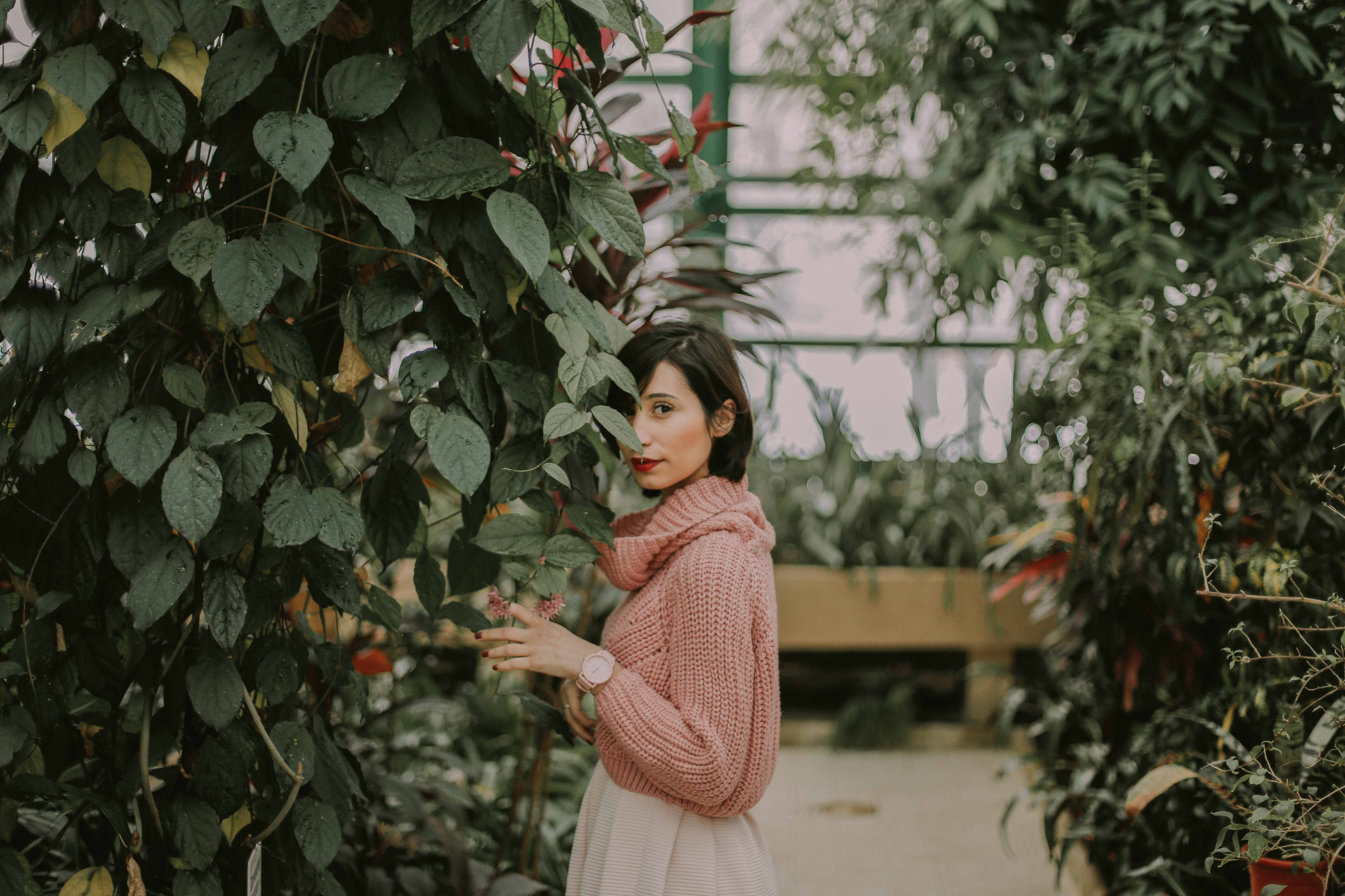A woman in a pink cowl-neck sweater stands against a plant in a greenhouse