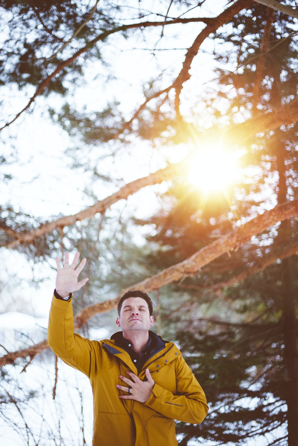 man raising left hand, right hand on chest closed eyes standing outdoor under shade of tree during daytime