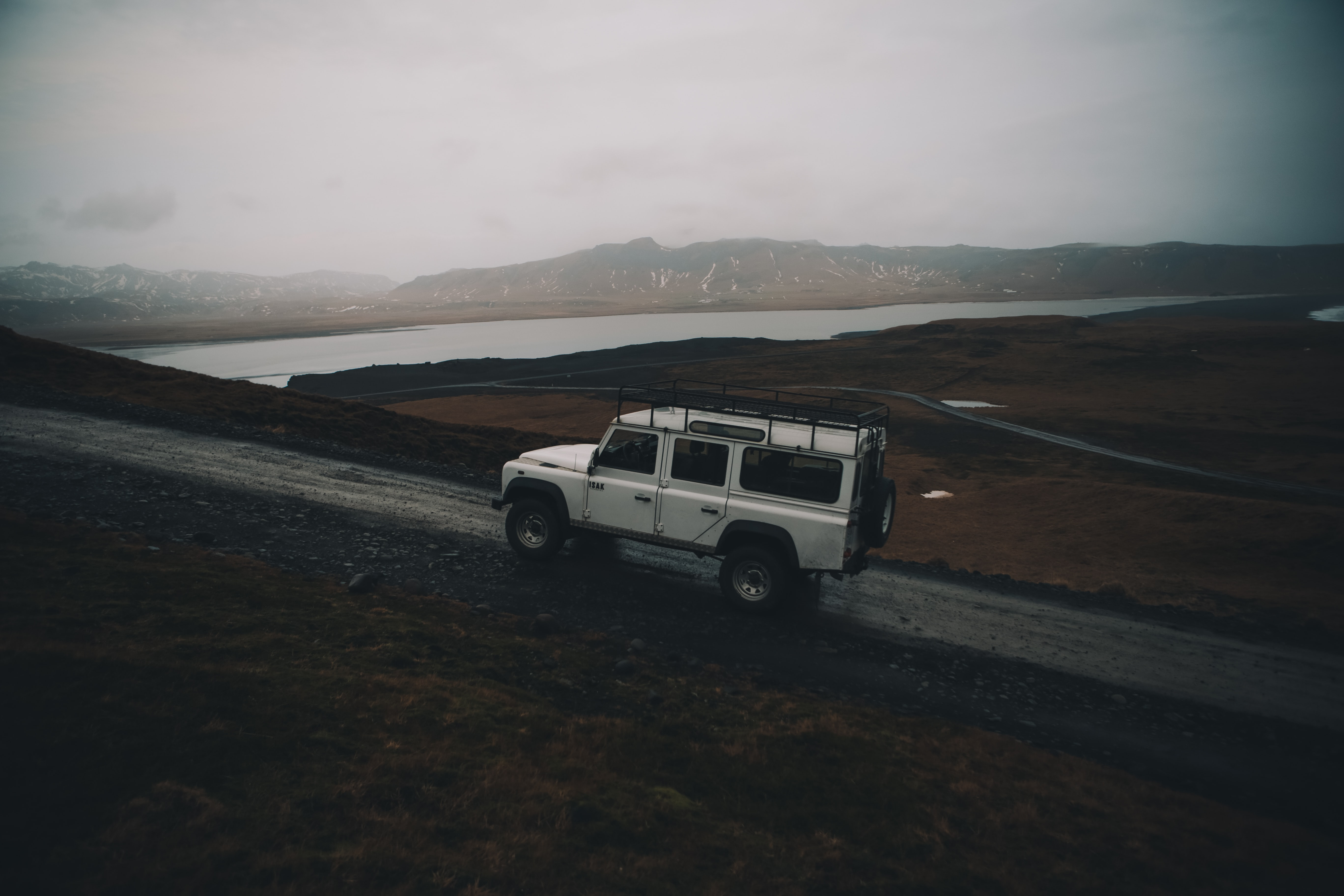 A white SUV driving up a dirt road in the mountains