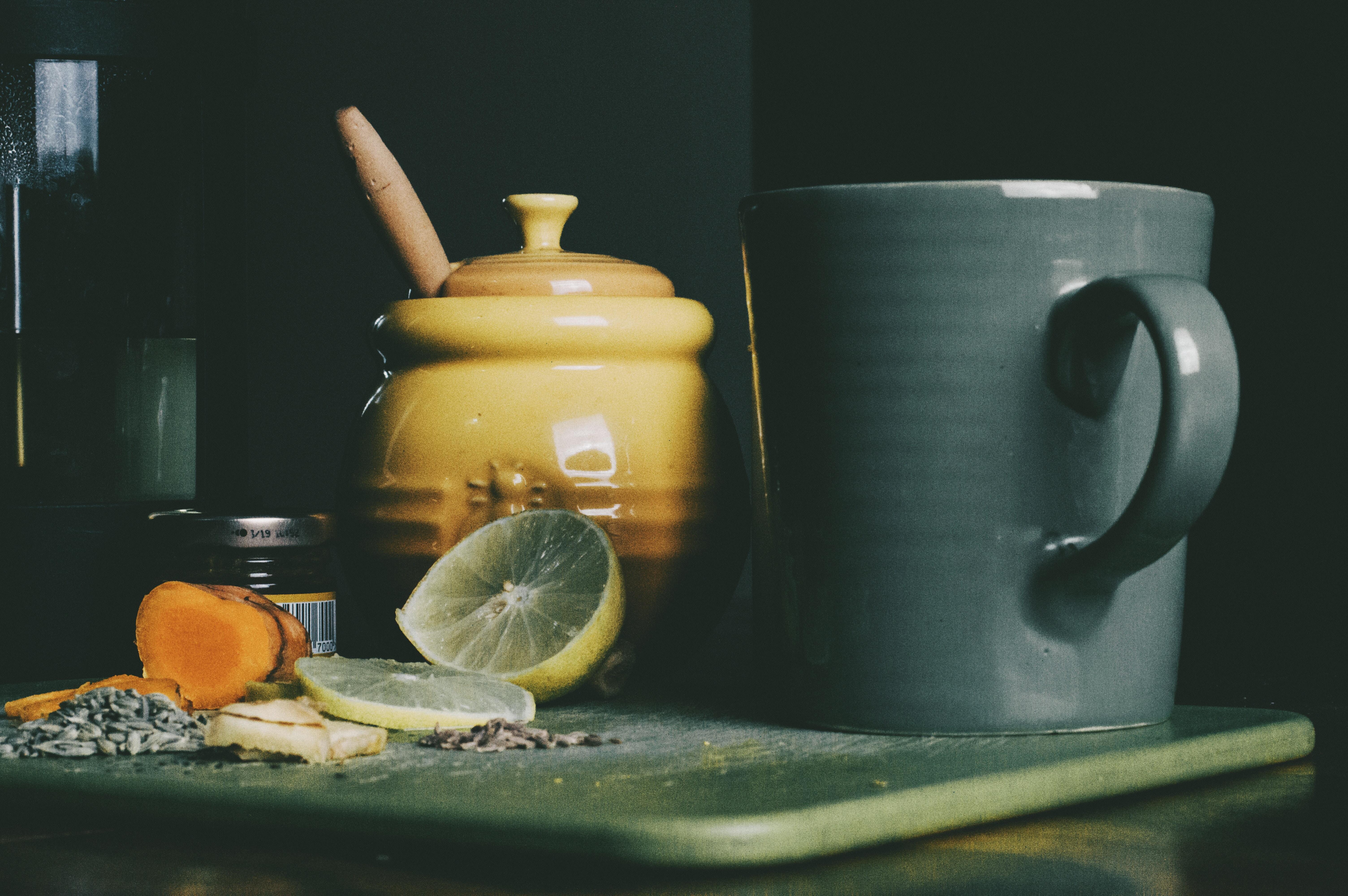 beige ceramic jar beside grey ceramic pitcher and sliced lemon fruit