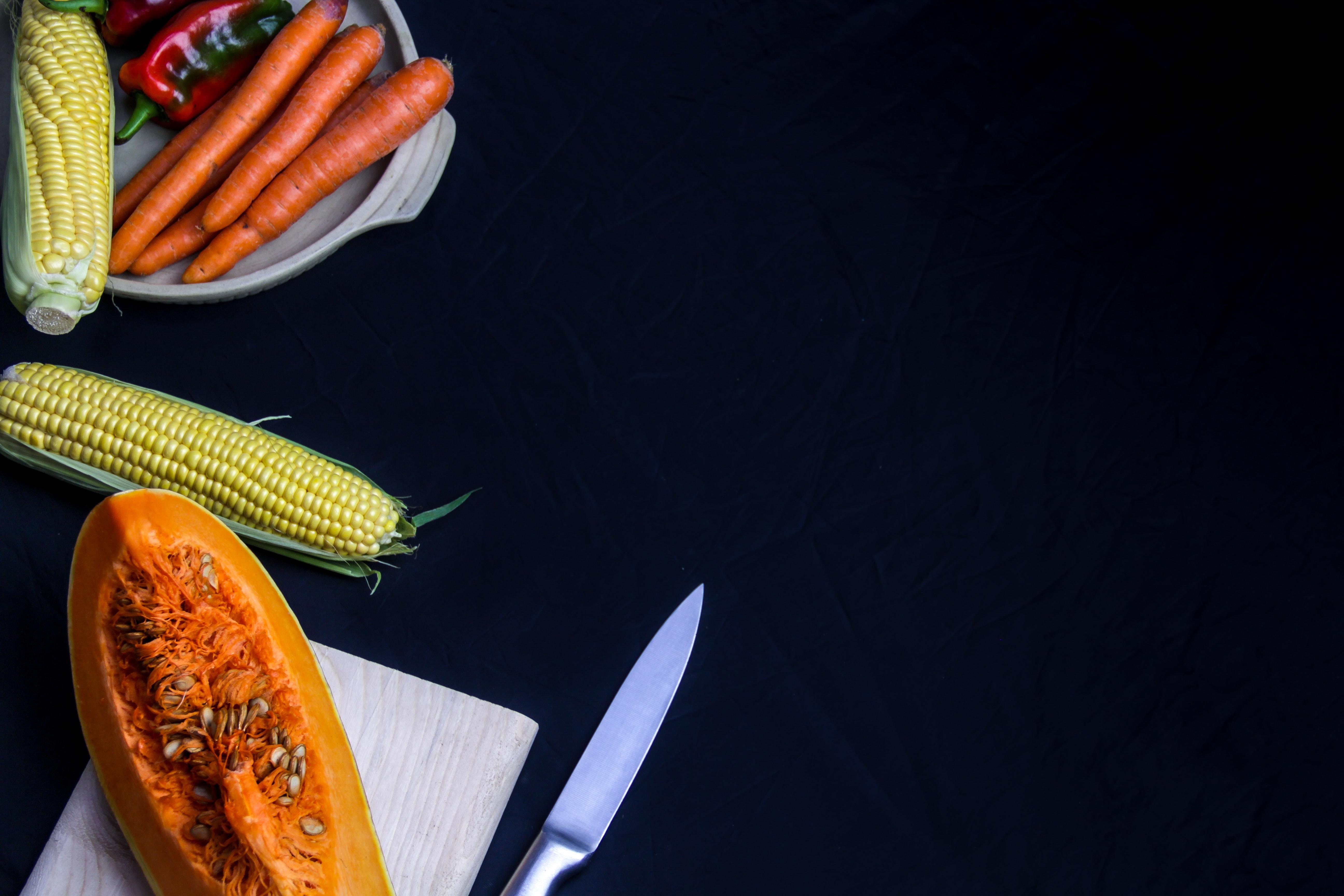 A flat lay shot of a knife, sweetcorns, pumpkins, carrots and various vegetables.