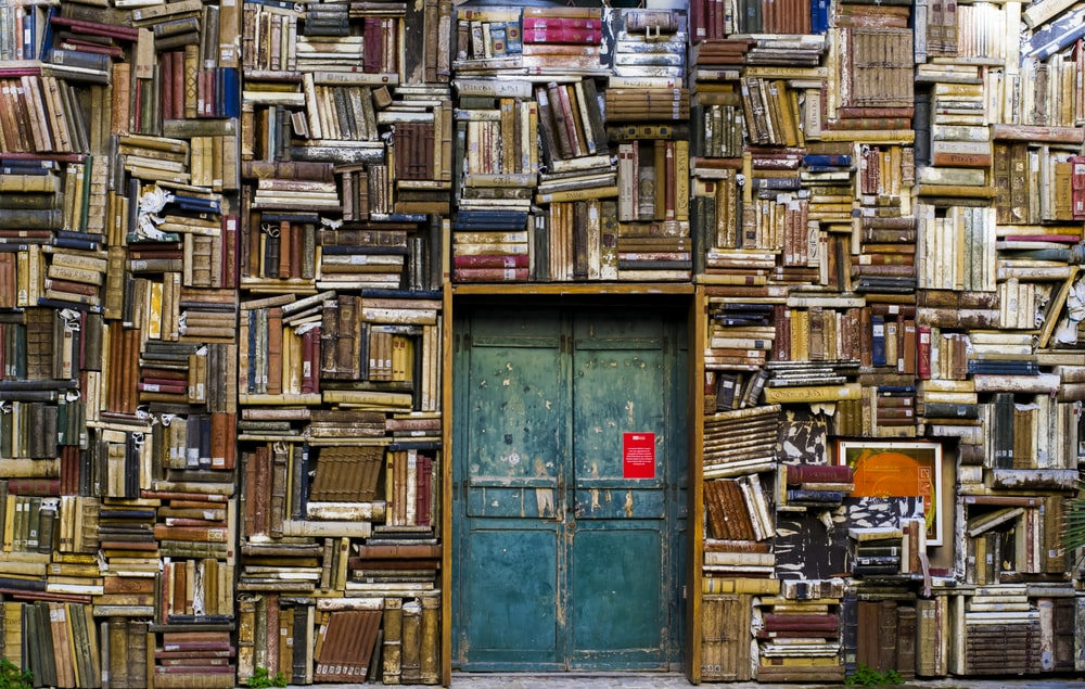 blue wooden door surrounded by book covered wall