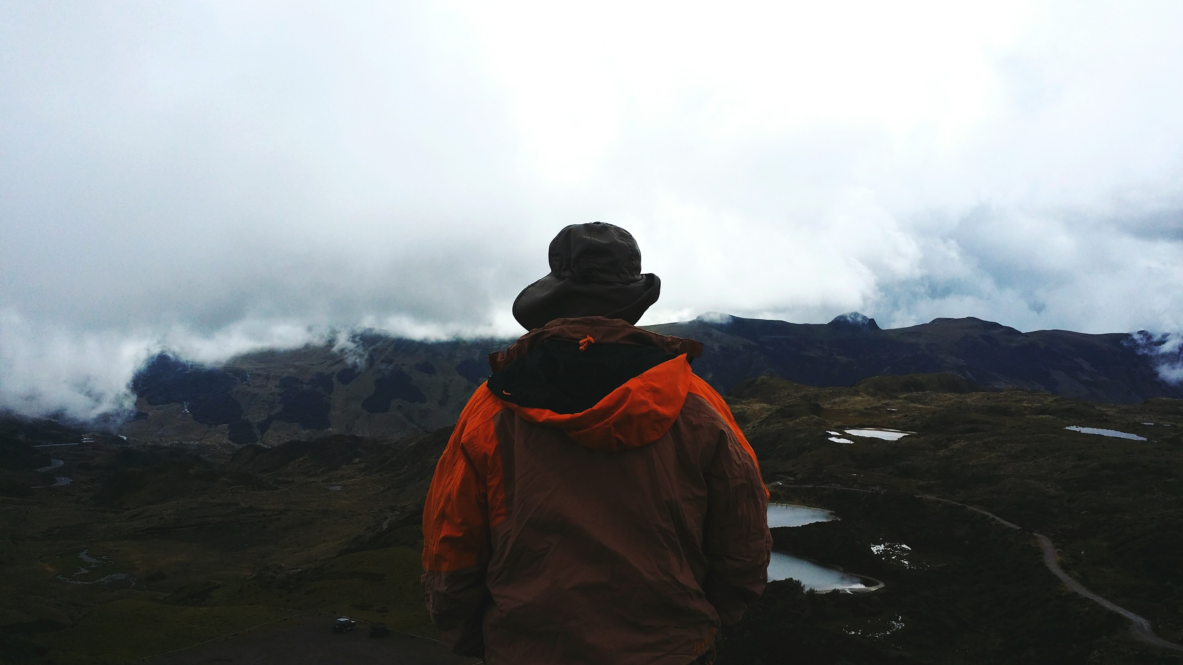 A person walking in a cloudy valley in Quito wearing a bright orange coat
