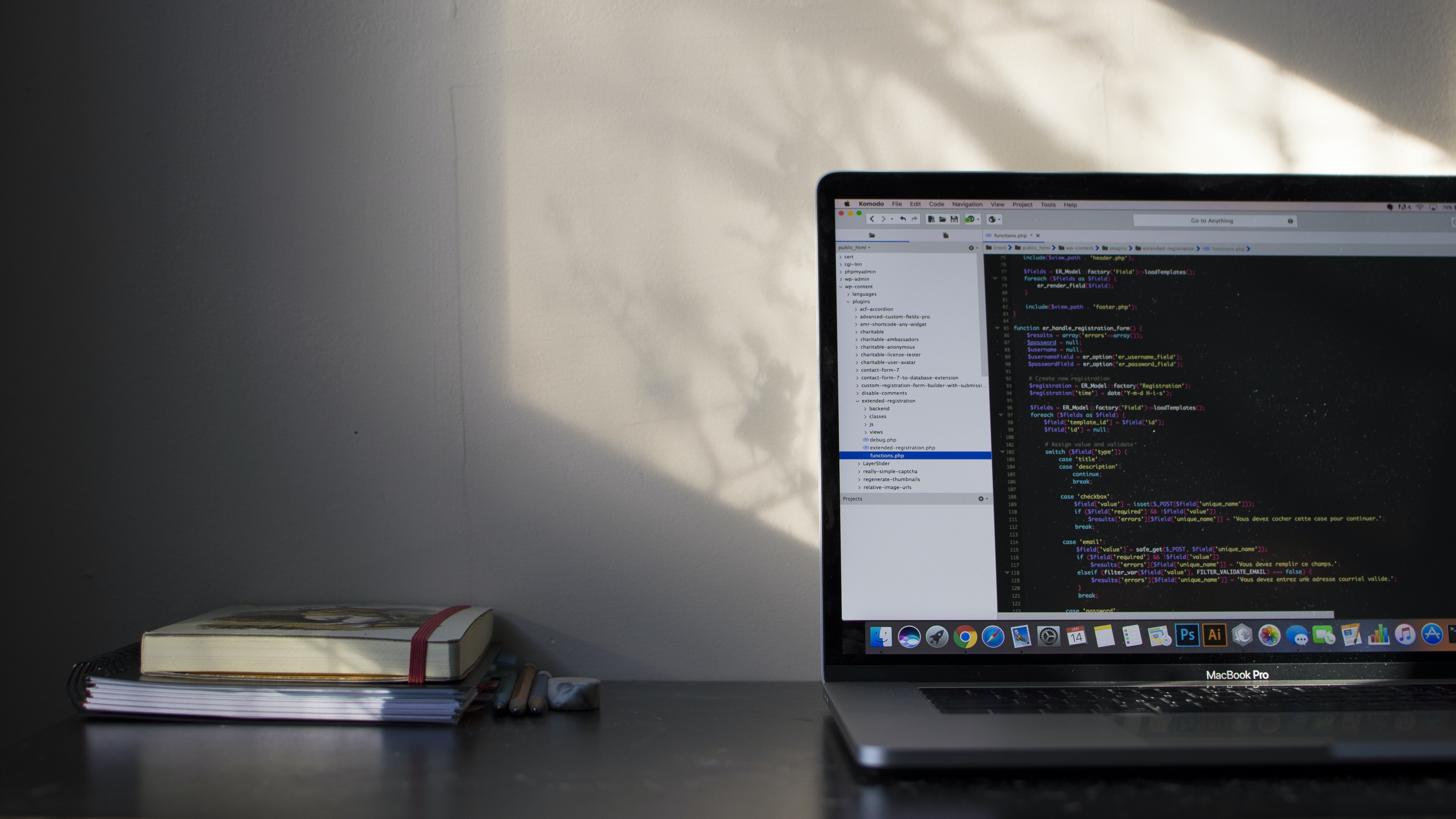 Two books on a desk near a MacBook with lines of code on its screen
