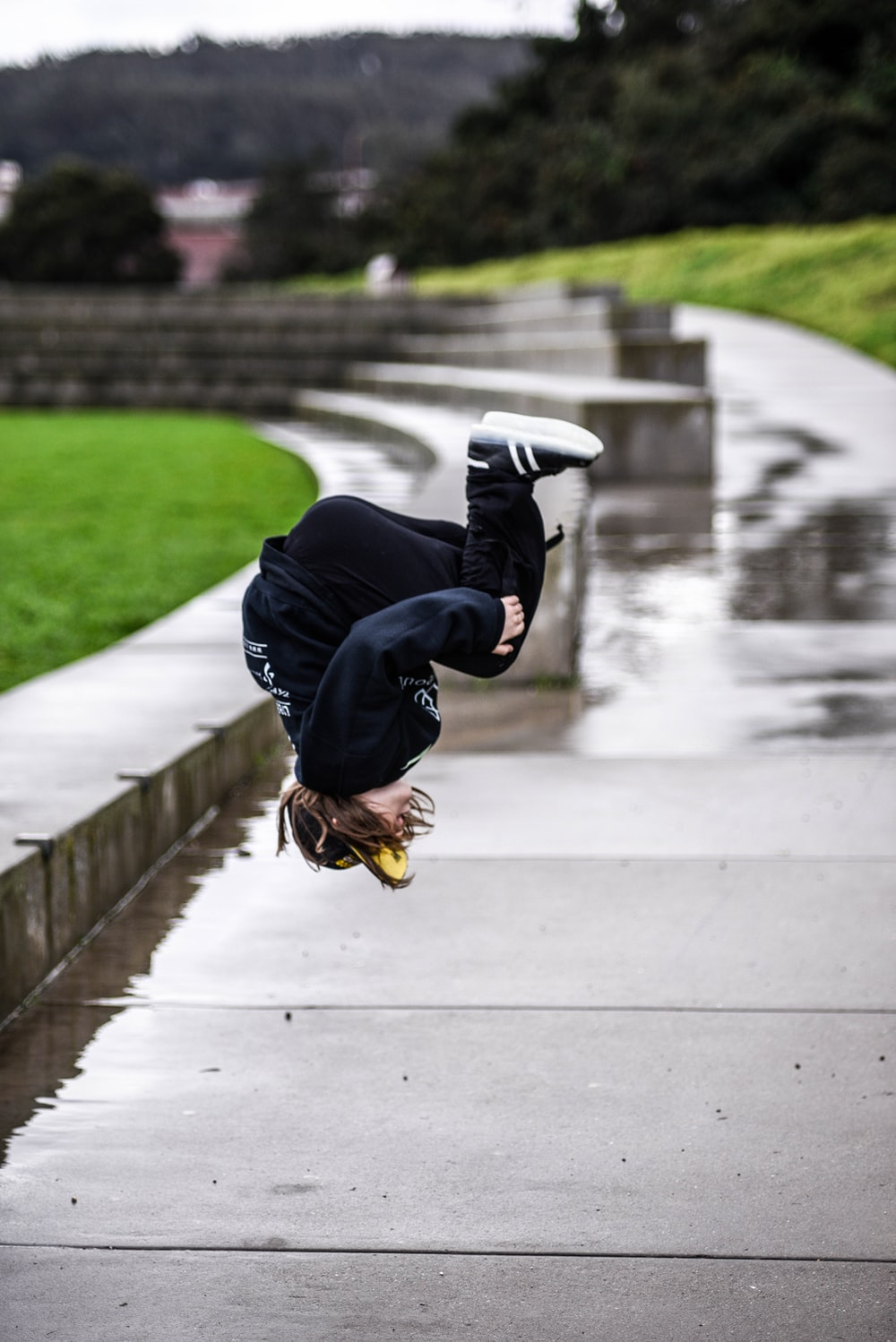 person wears black jacket and black pants doing flip on gray concrete walkway with water during daytime selective focus photography