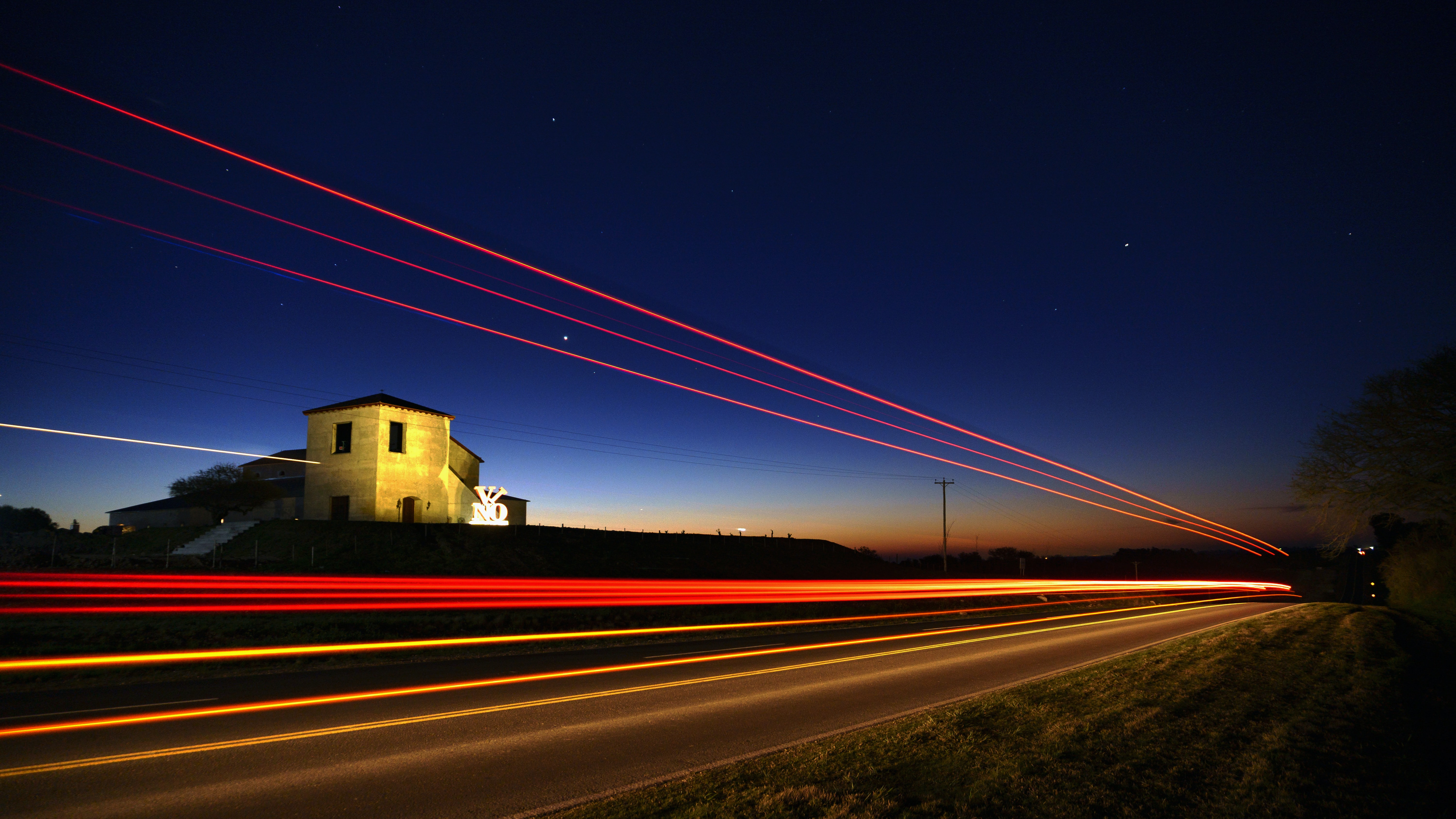 A gleaming red light trail shining down a dark road in Victoria