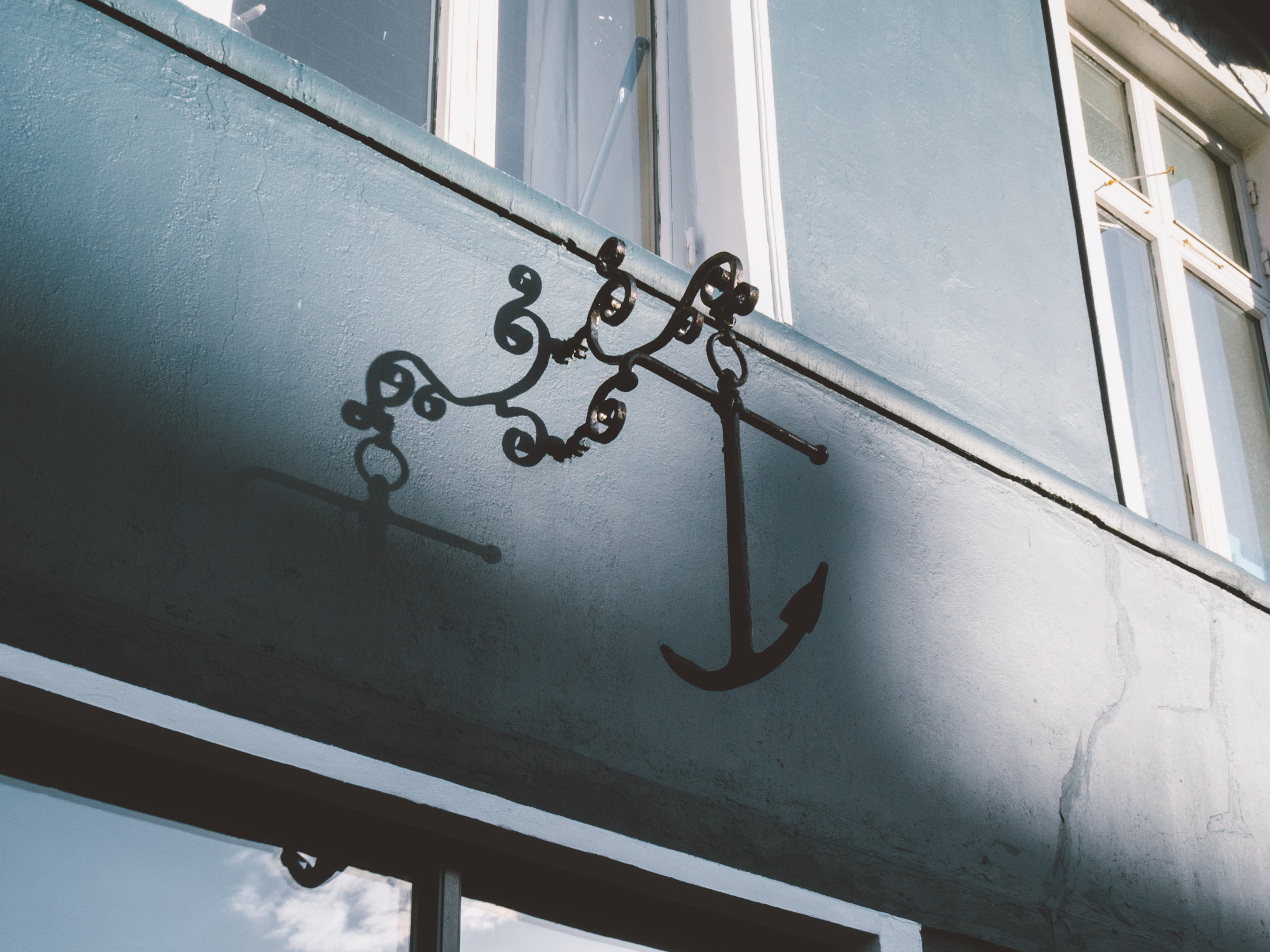 A steel anchor fixture on a blue building wall