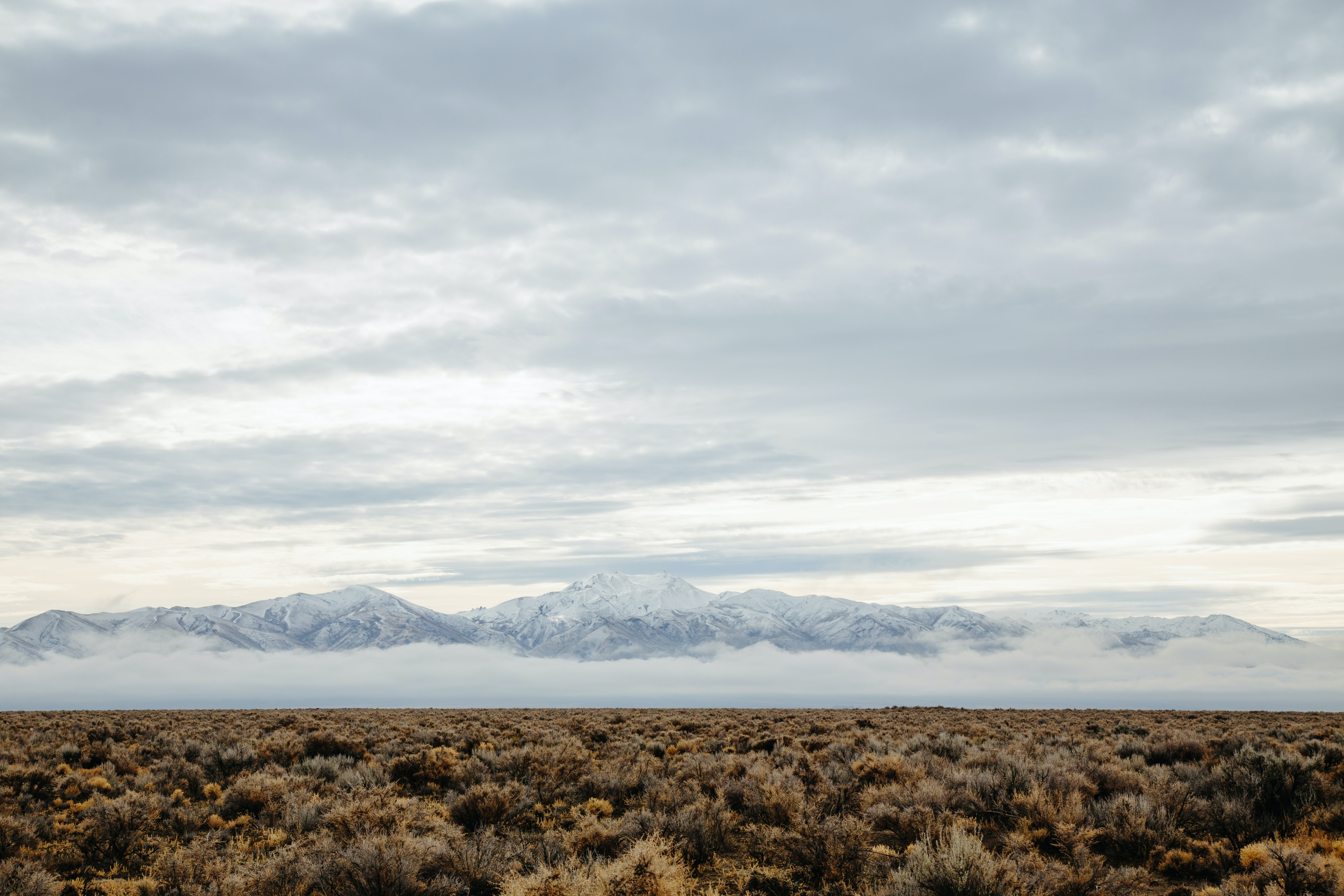 barren field across mountain range photo during cloudy day
