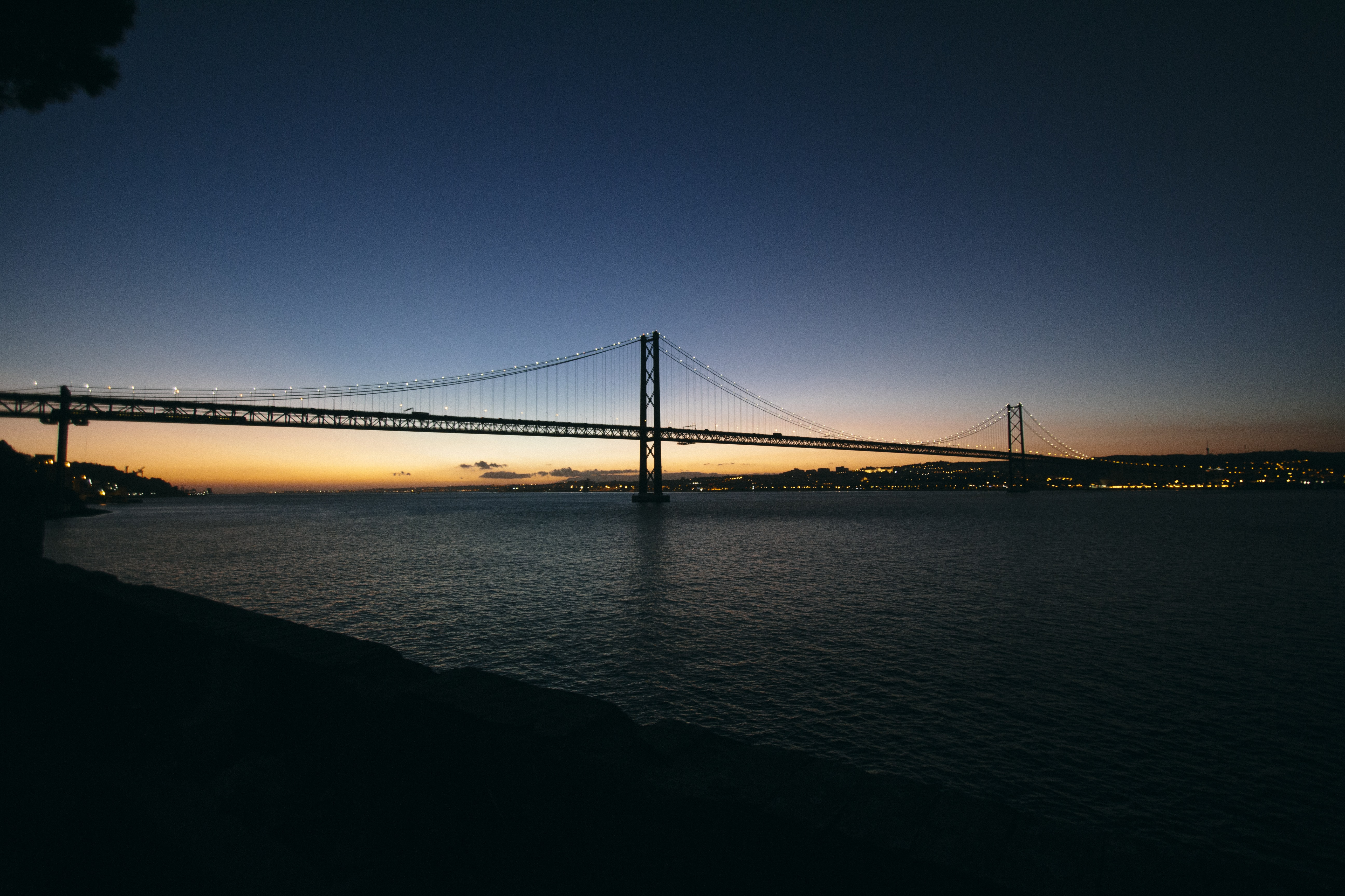 The end of a sunset behind a large suspension bridge over water in Lisbon.