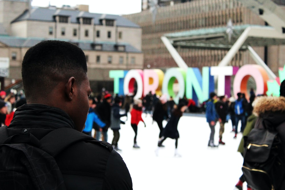 man wearing black backpack ice skating with other people near Toronto freestanding decor during daytime