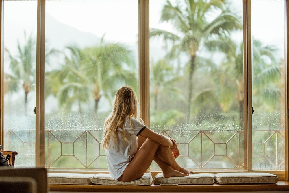 woman sitting on white cushion near glass window