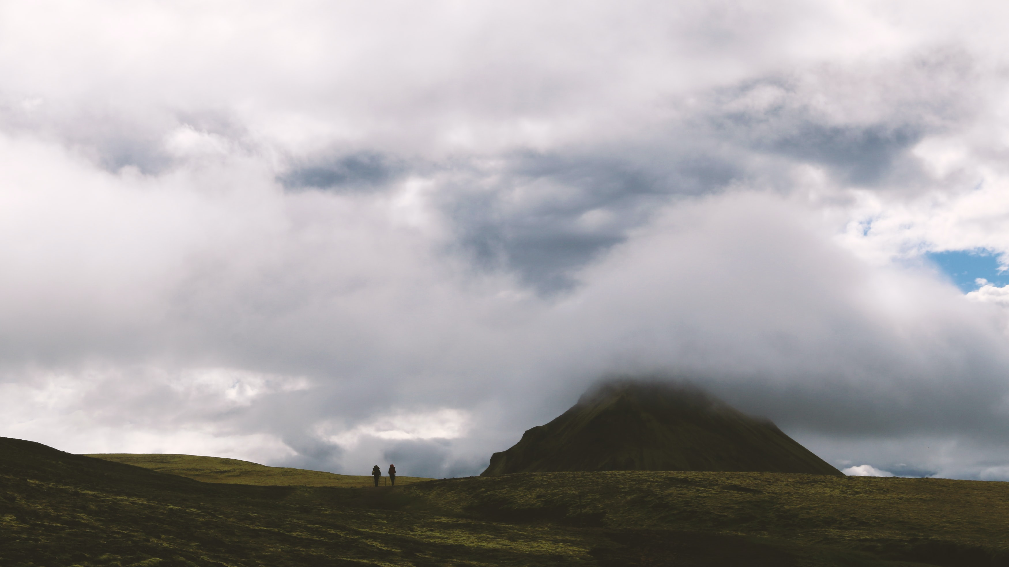 Two people hiking across grassy plain underneath cloudy sky