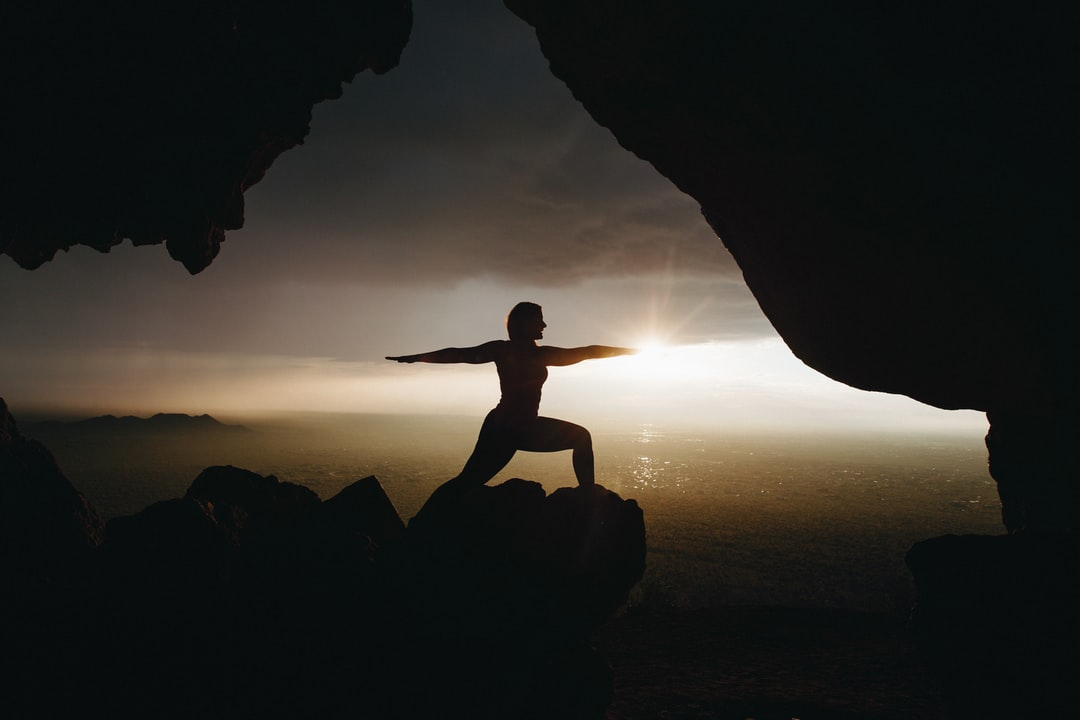 A person does yoga at a cave mouth as the sun rises in front over a calm sea.