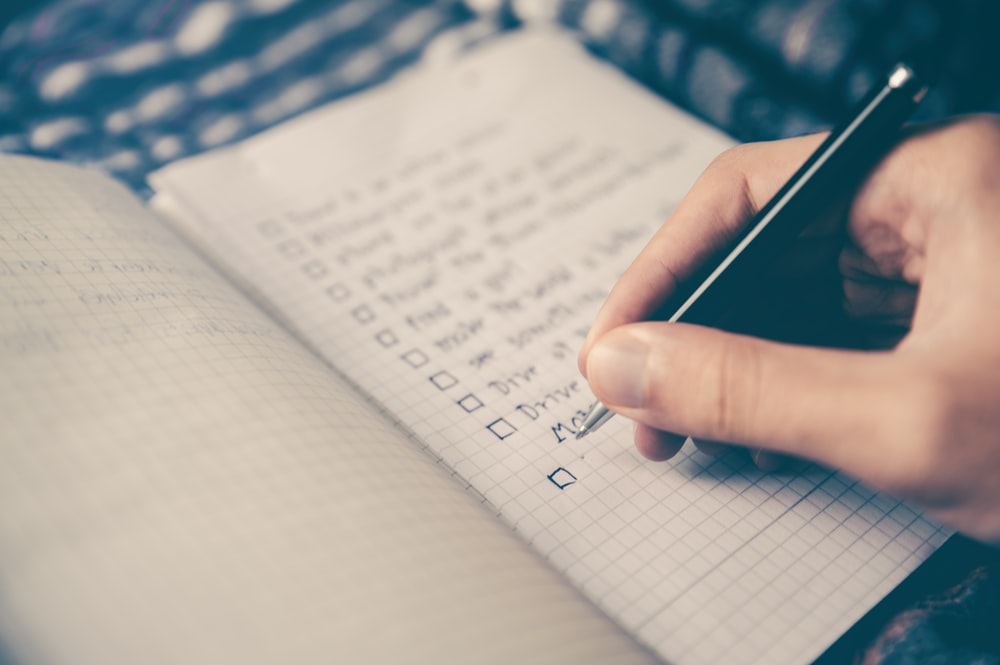 A person making a checklist in a notebook