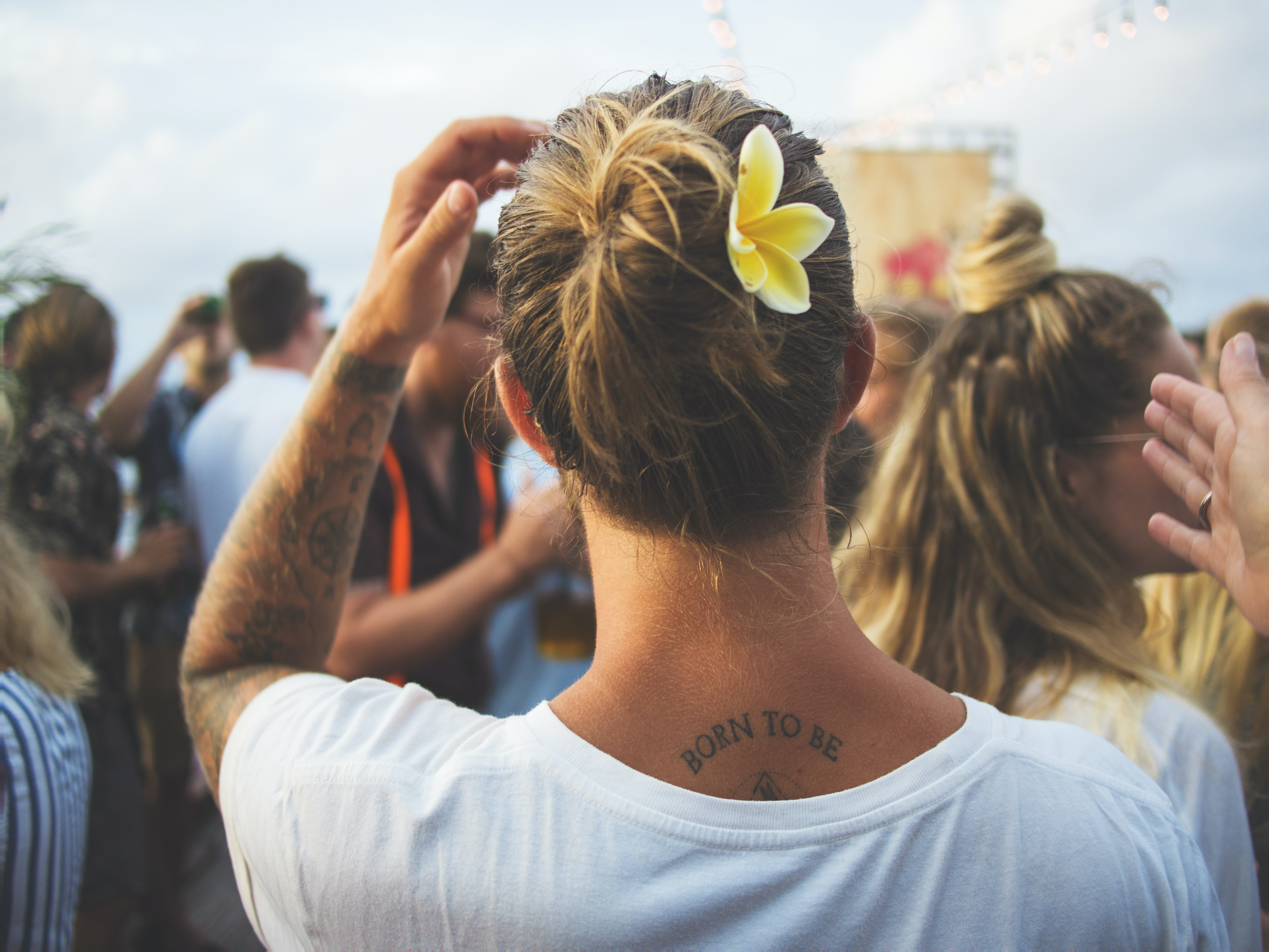 A person with tattoos and a flower in their hair looks toward a festival crowd