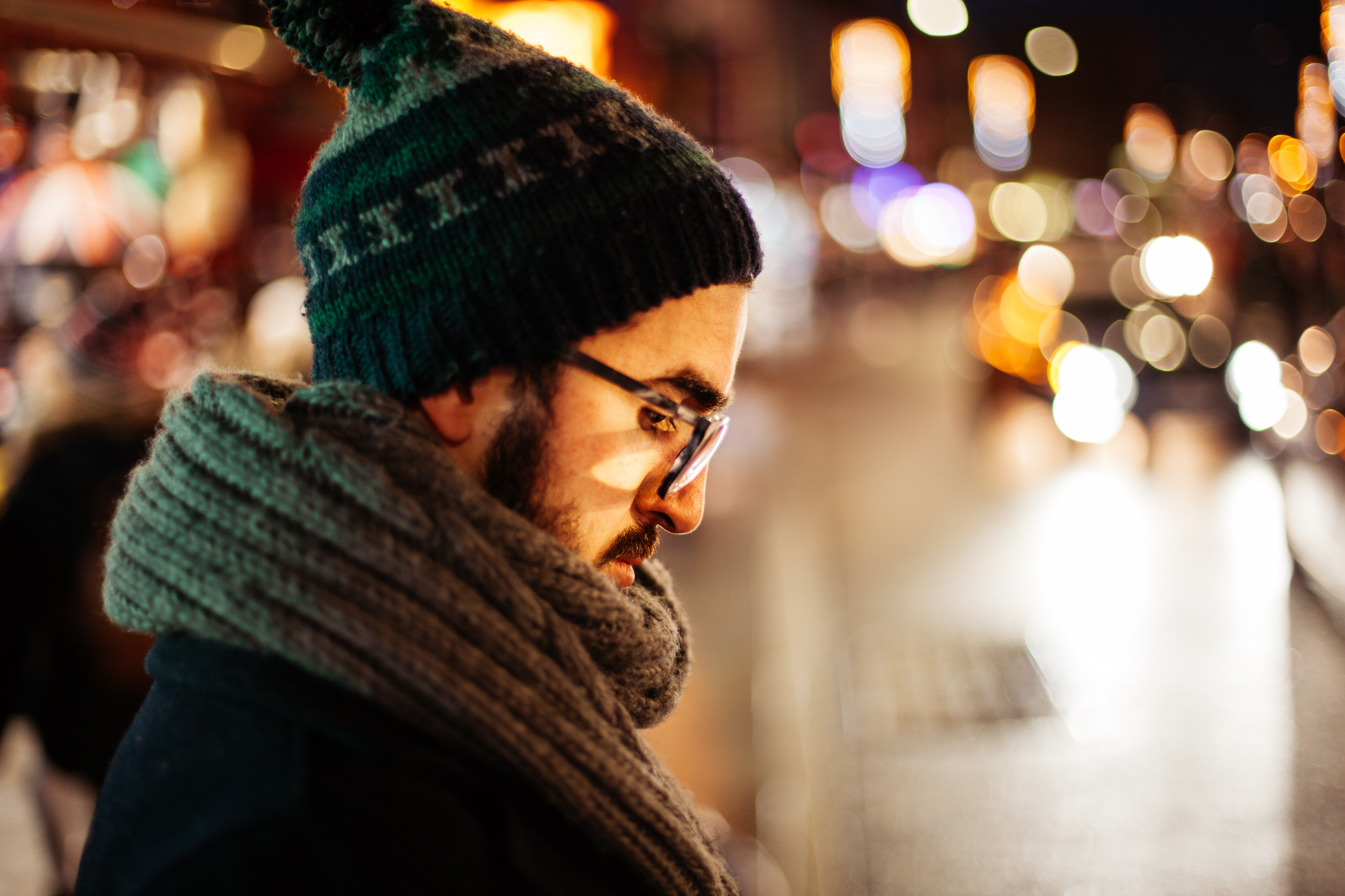 A bearded man in a winter cap and thick scarf with bokeh effect in the background.