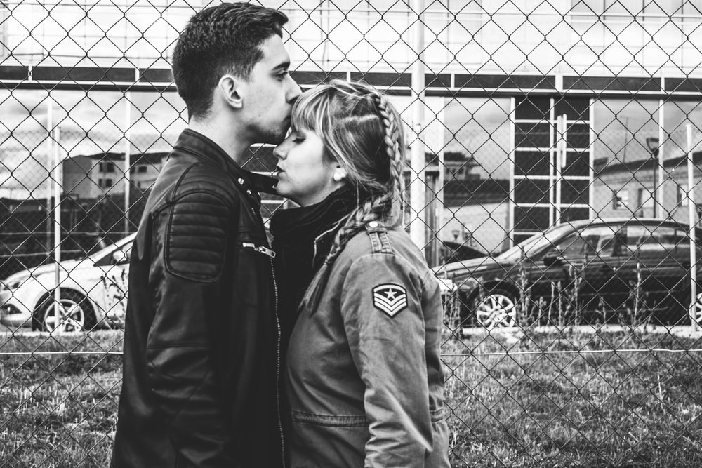 grayscale photo of man kissing forehead of woman near fence