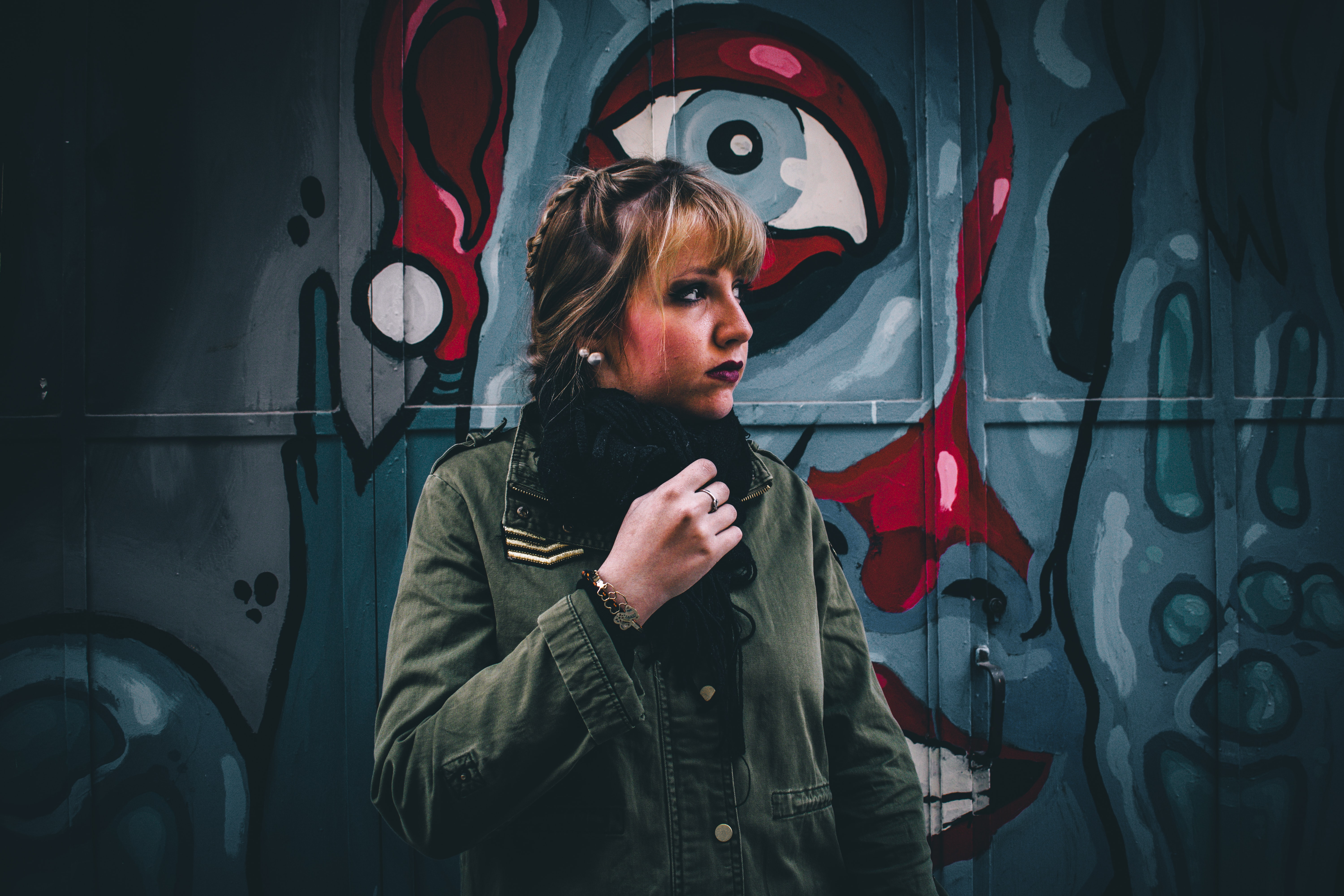 Young attractive blonde woman in front of haunting graffiti with eye in Salamanca