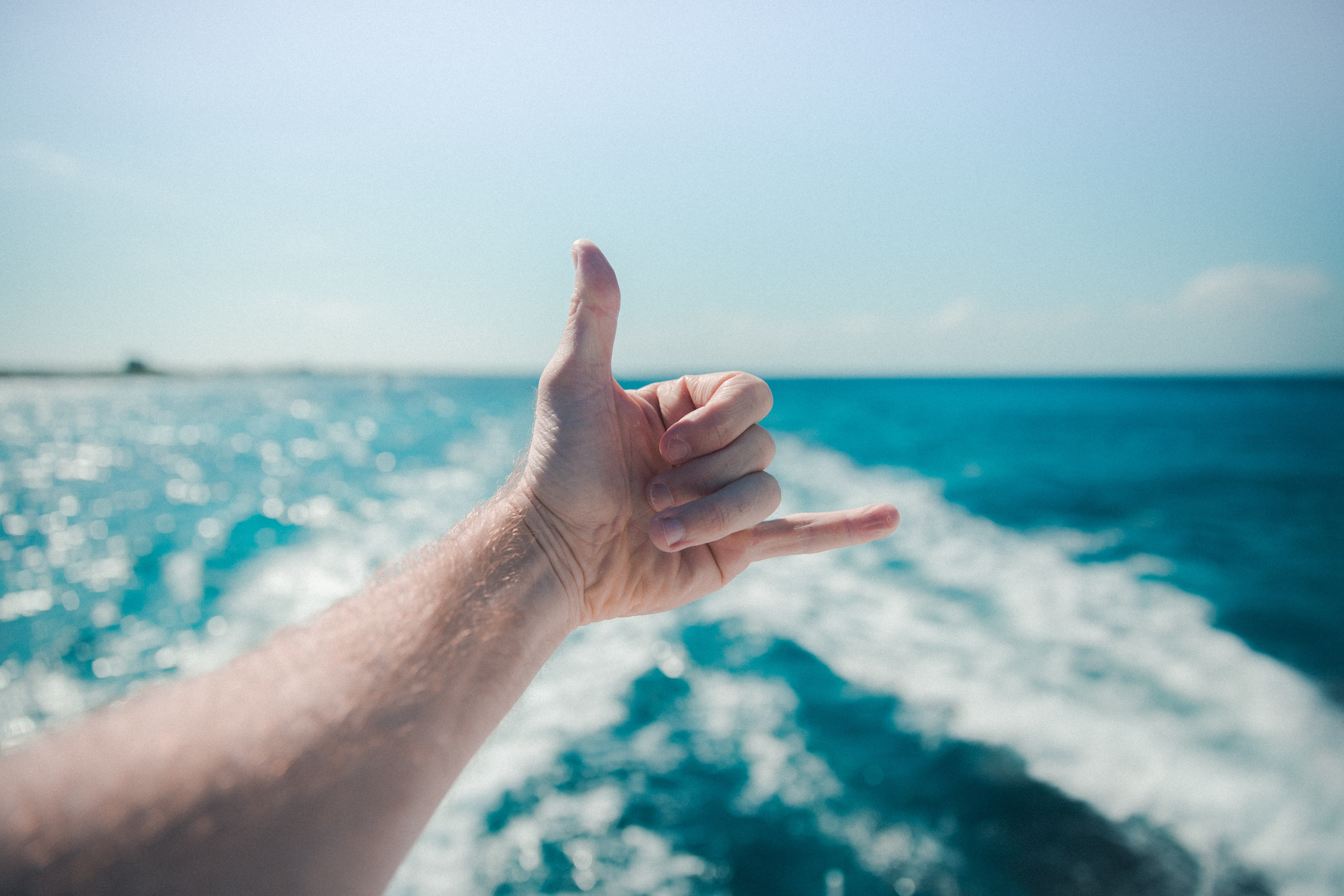 """An outstretched hand making a """"telephone"""" gesture over the white wake left in the sea by the boat"""