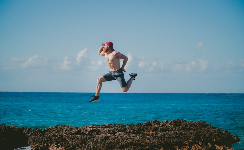 man jumping in mid air while looking ahead beside body of water during daytime