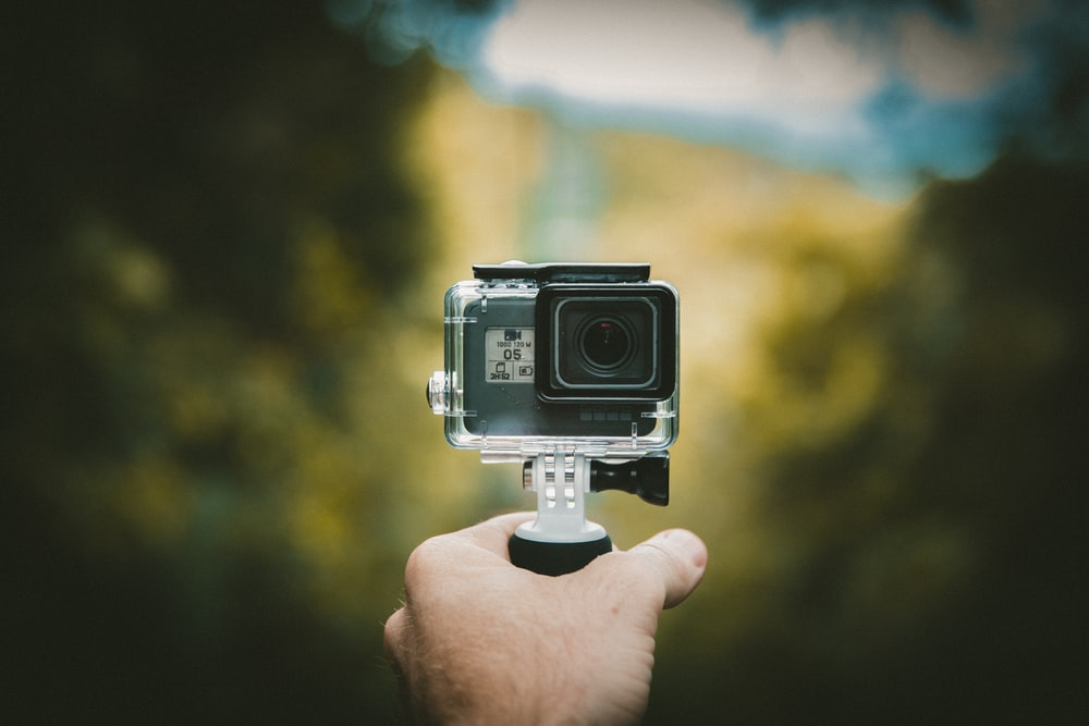 person holding action camera