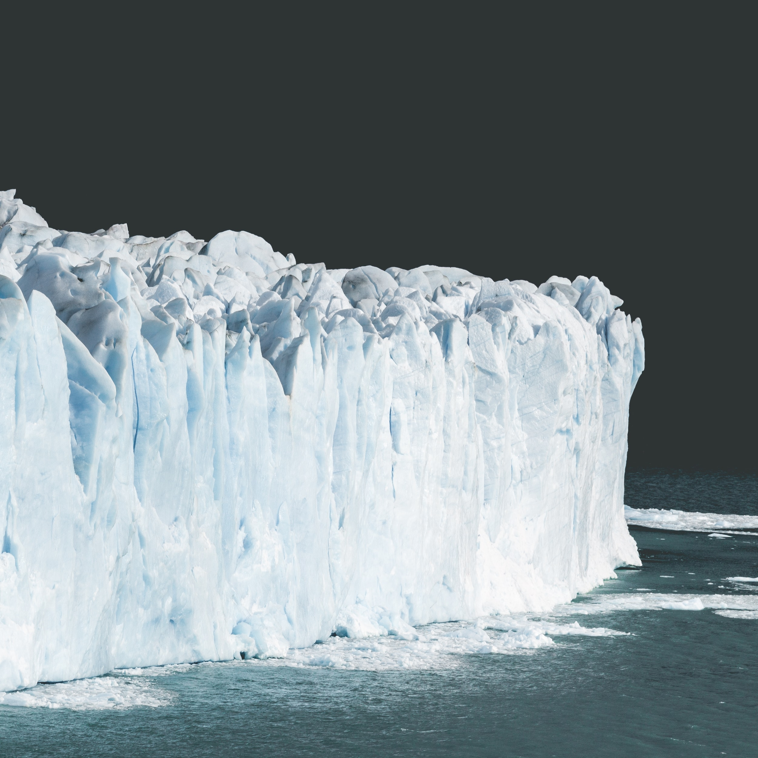 A giant wall of ice sits in the ocean against a dark sky