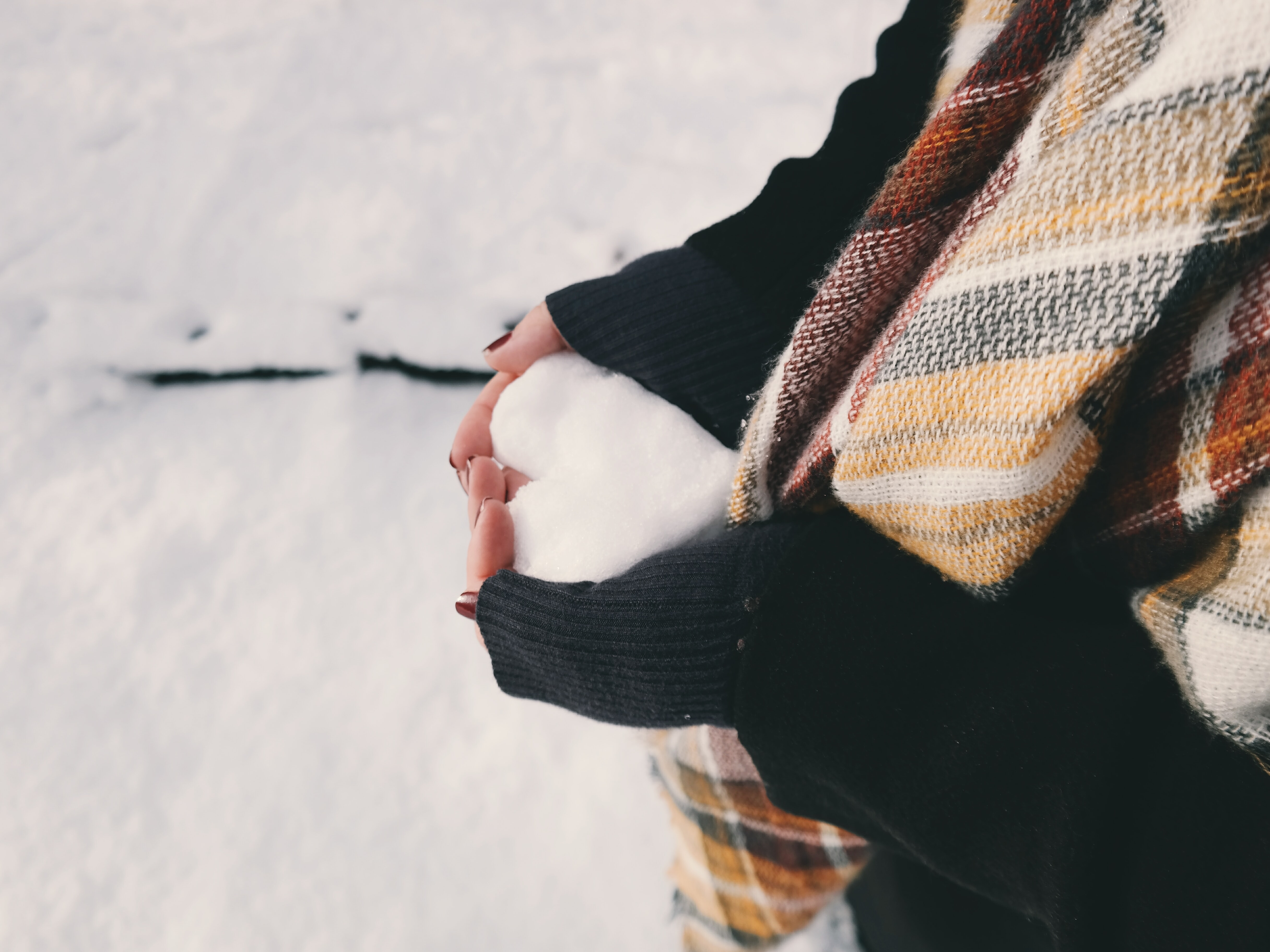 An overhead shot of a person's hands clutching a heart-shaped clump of snow