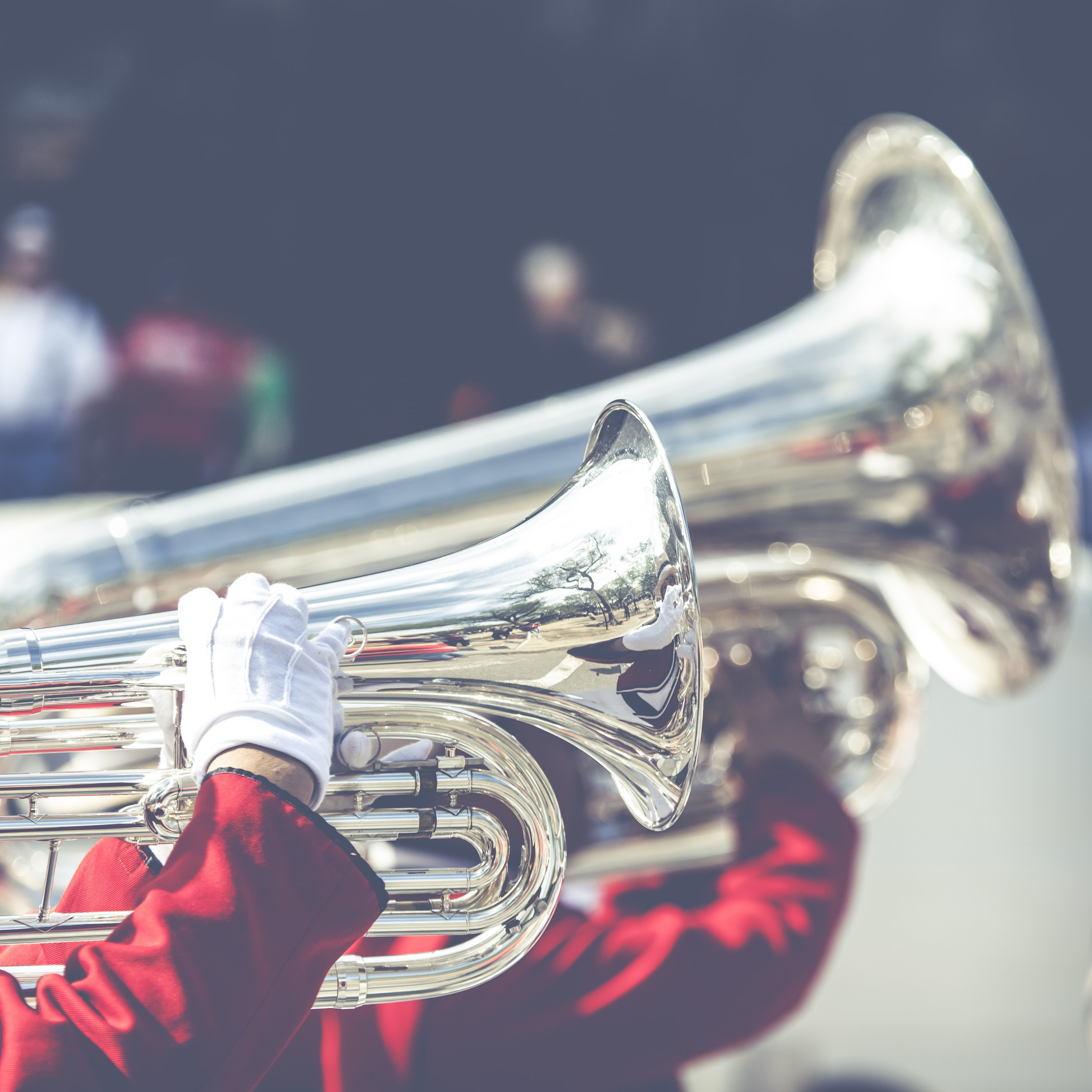 A band in red suits and white gloves playing trumpets