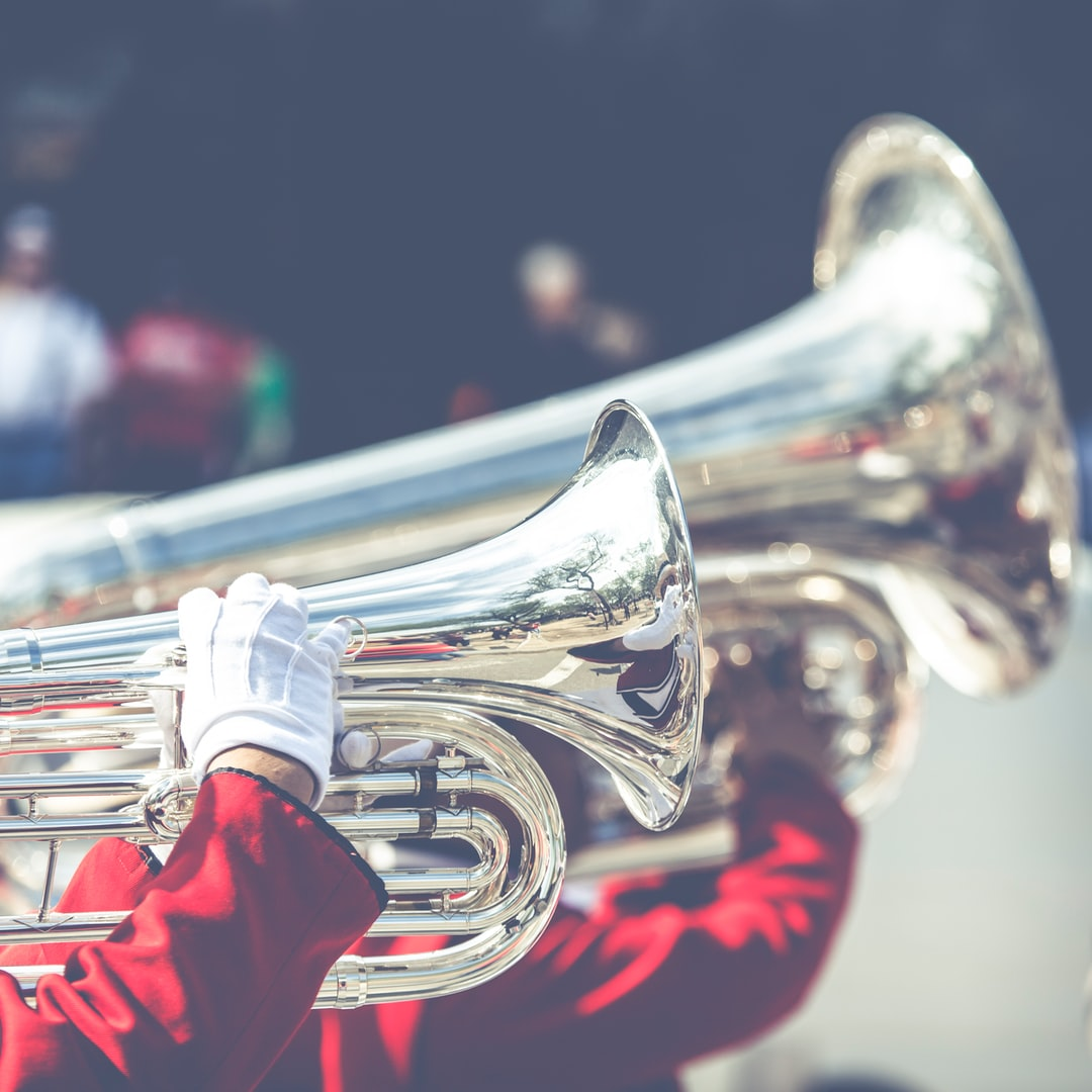 Hands of the man playing the trumpet in parade in USA.