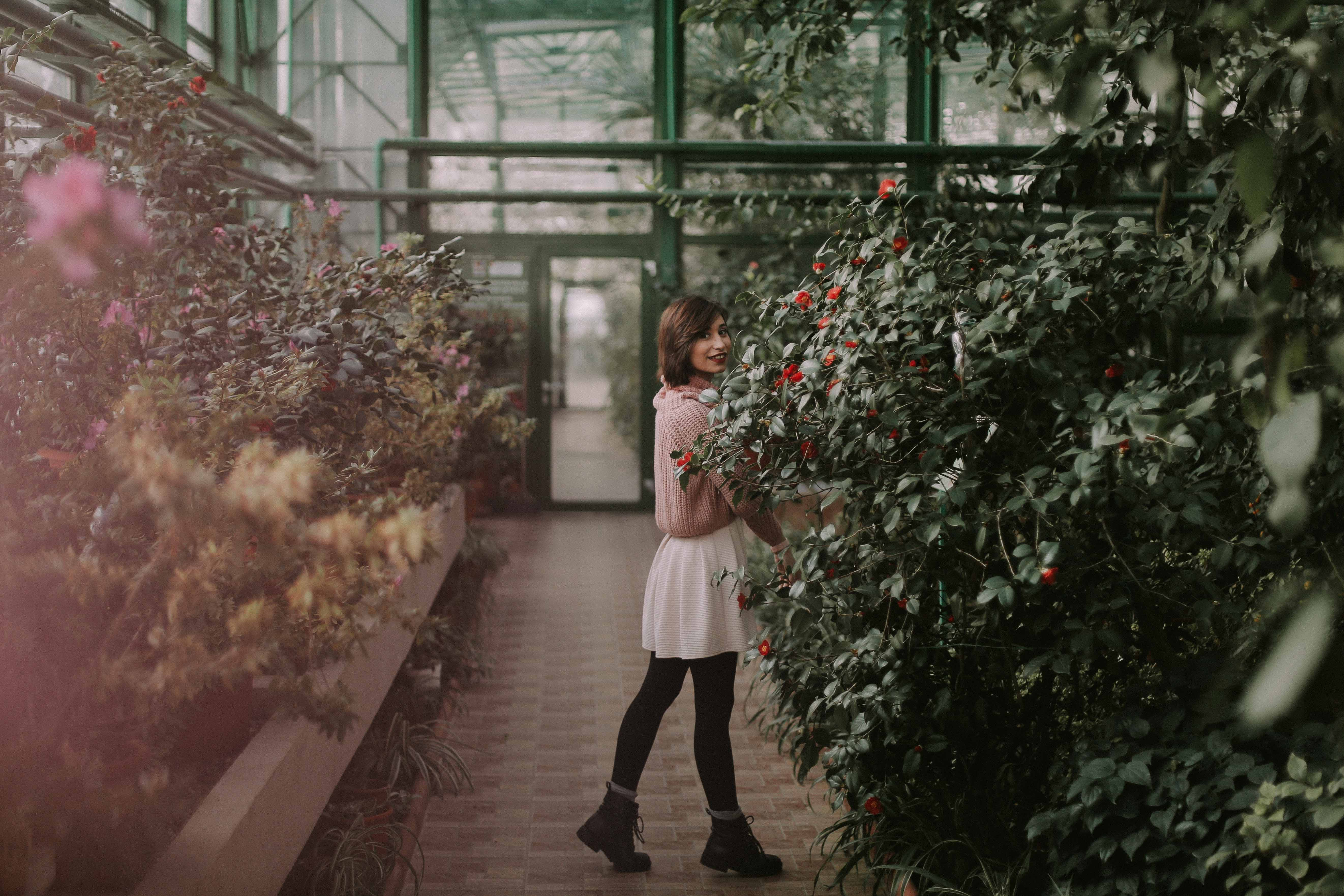 A young woman smiling to the camera in a botanical garden