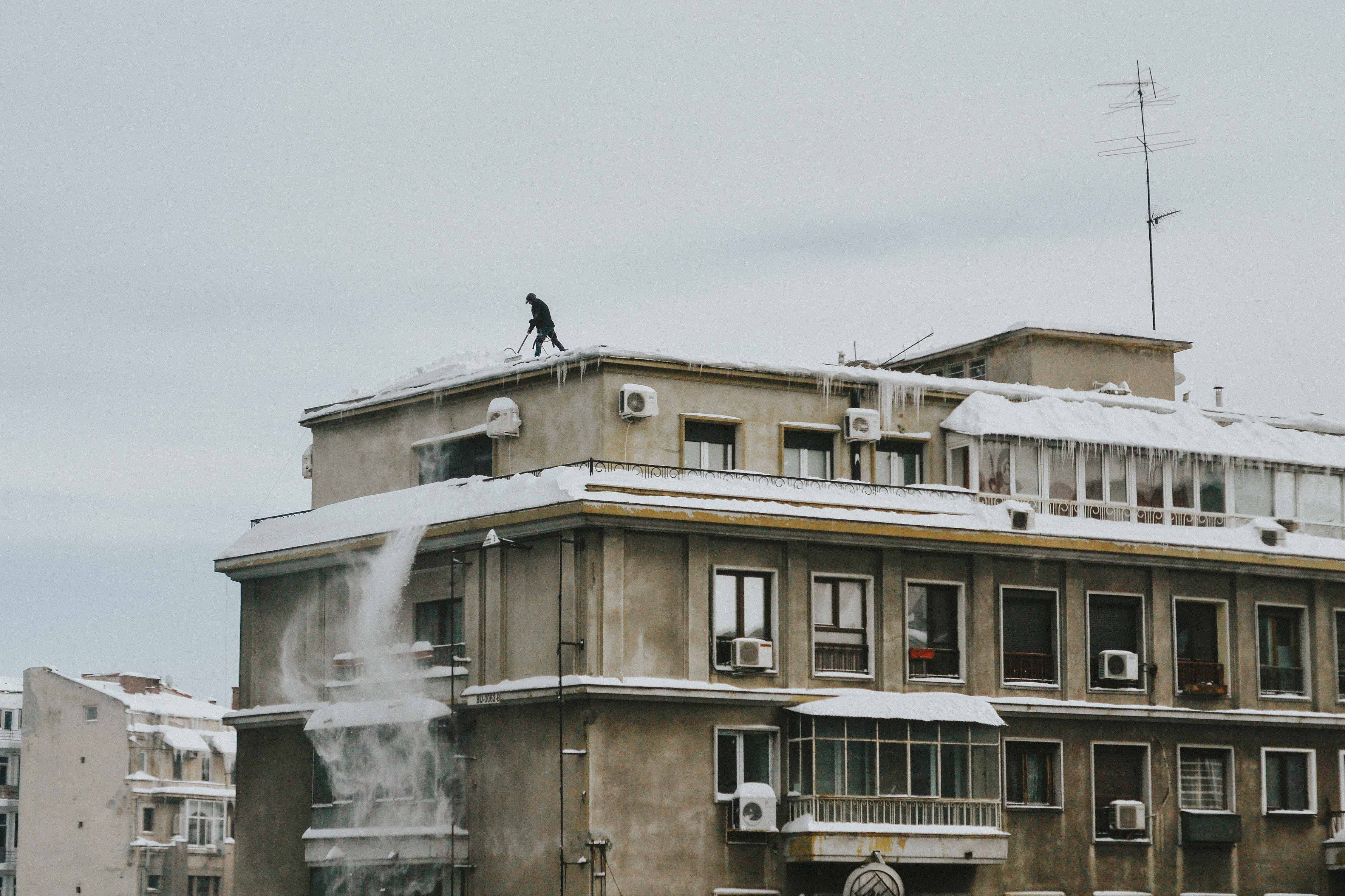 A person sweeping snow off the roof of a residential building