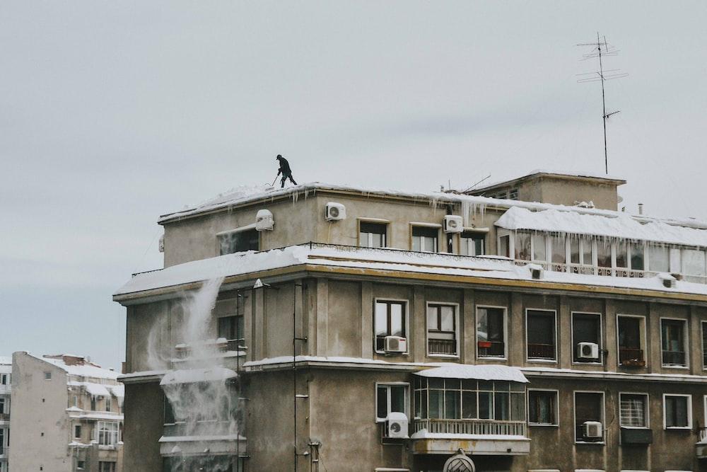 man on brown concrete building