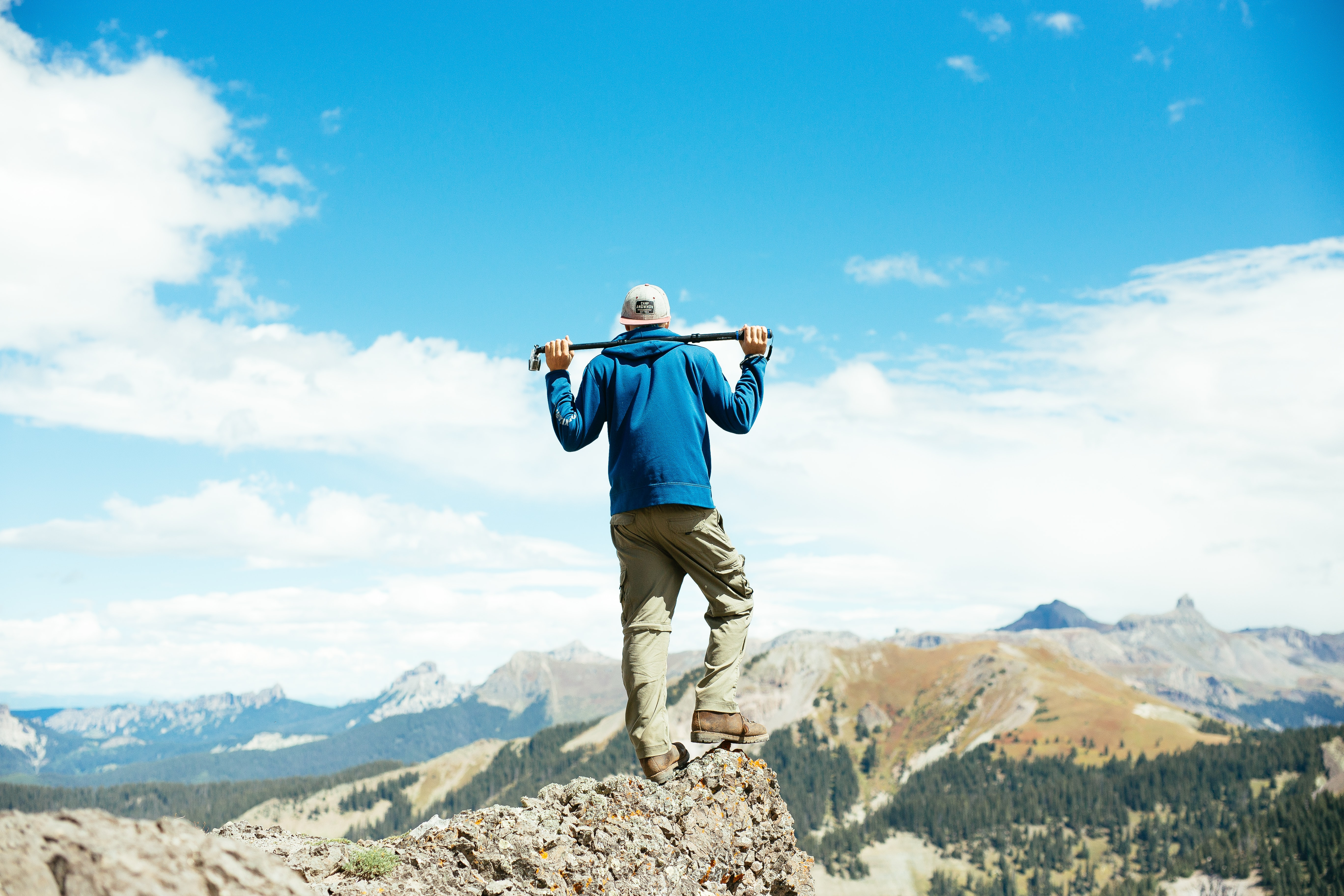 A man holding a hiking stick behind his back while staring over the landscape at the Bridge of Heaven