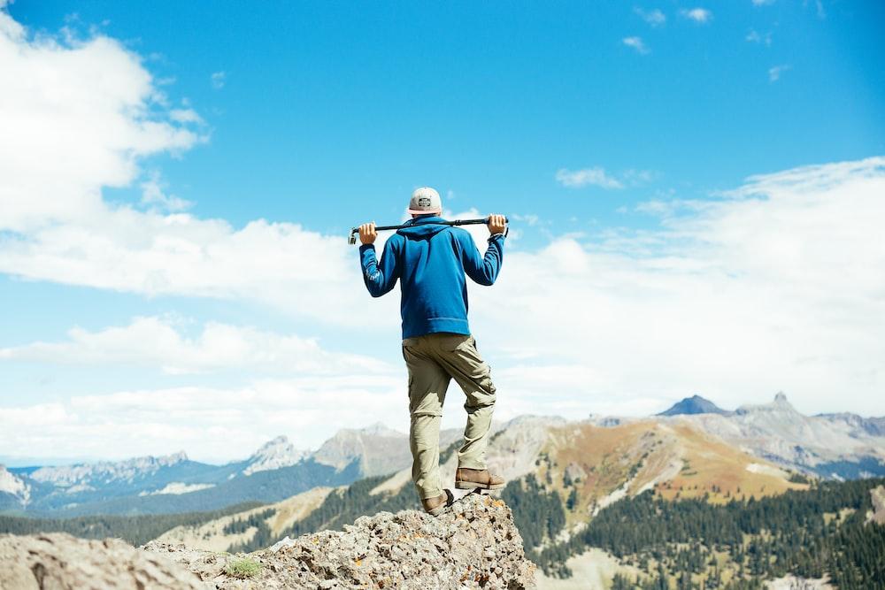 man holding bar on mountain peak during daytime