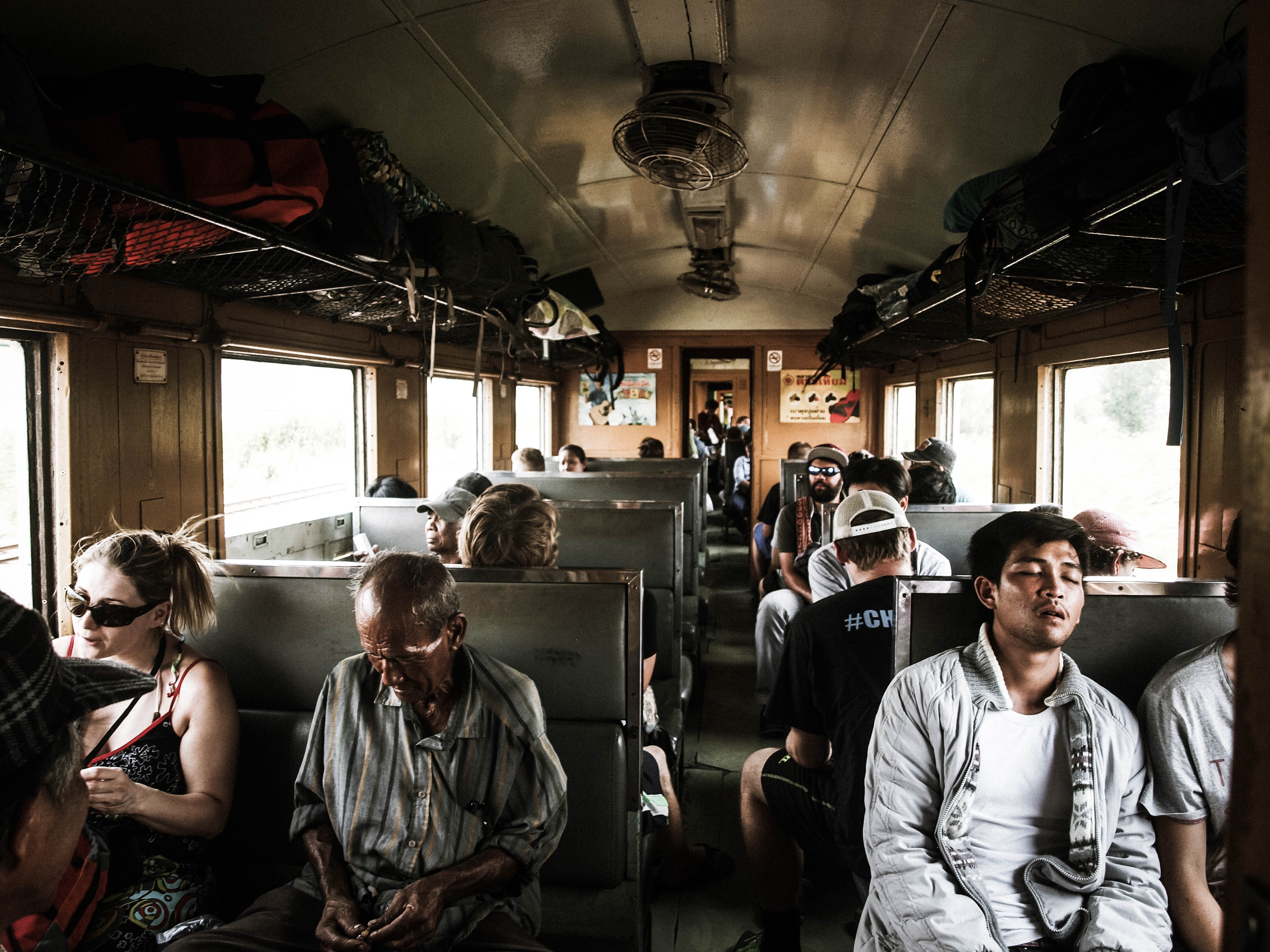 Diverse crowd of commuters sit and sleep on a busy train