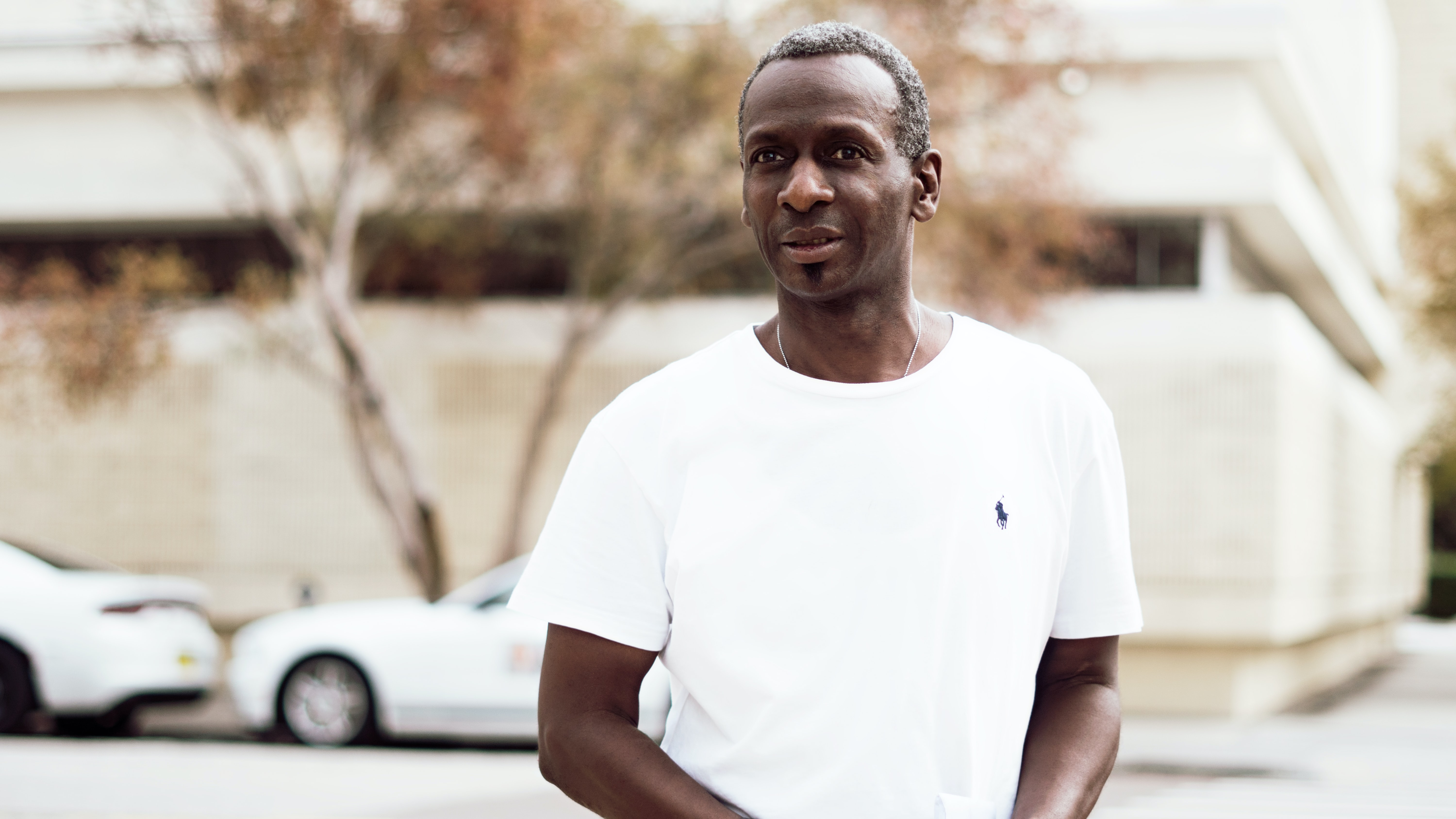 A man wearing white t-shirt standing on the street