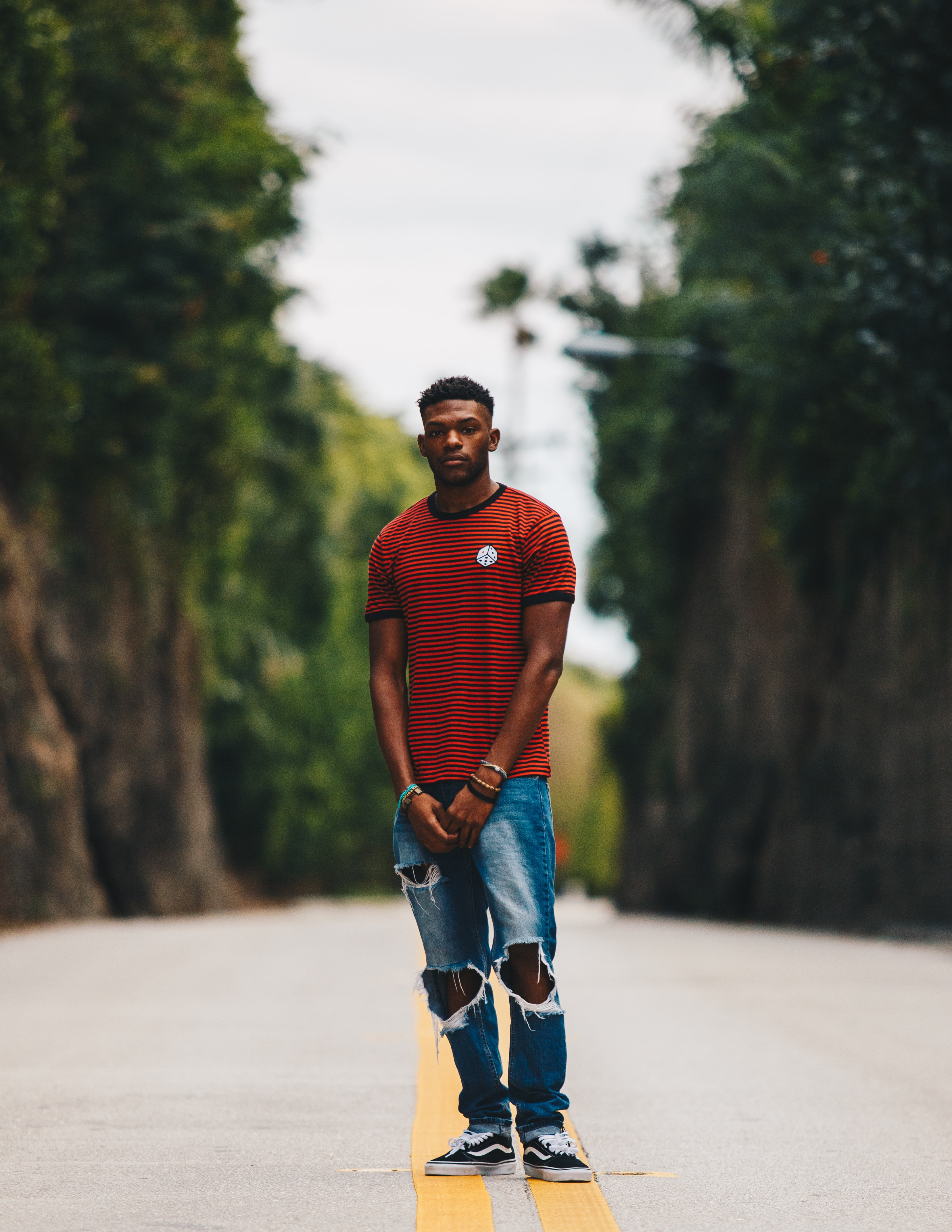 Photo of a Black man in a red striped shirt and ripped blue jeans standing in the middle of a scenic road.
