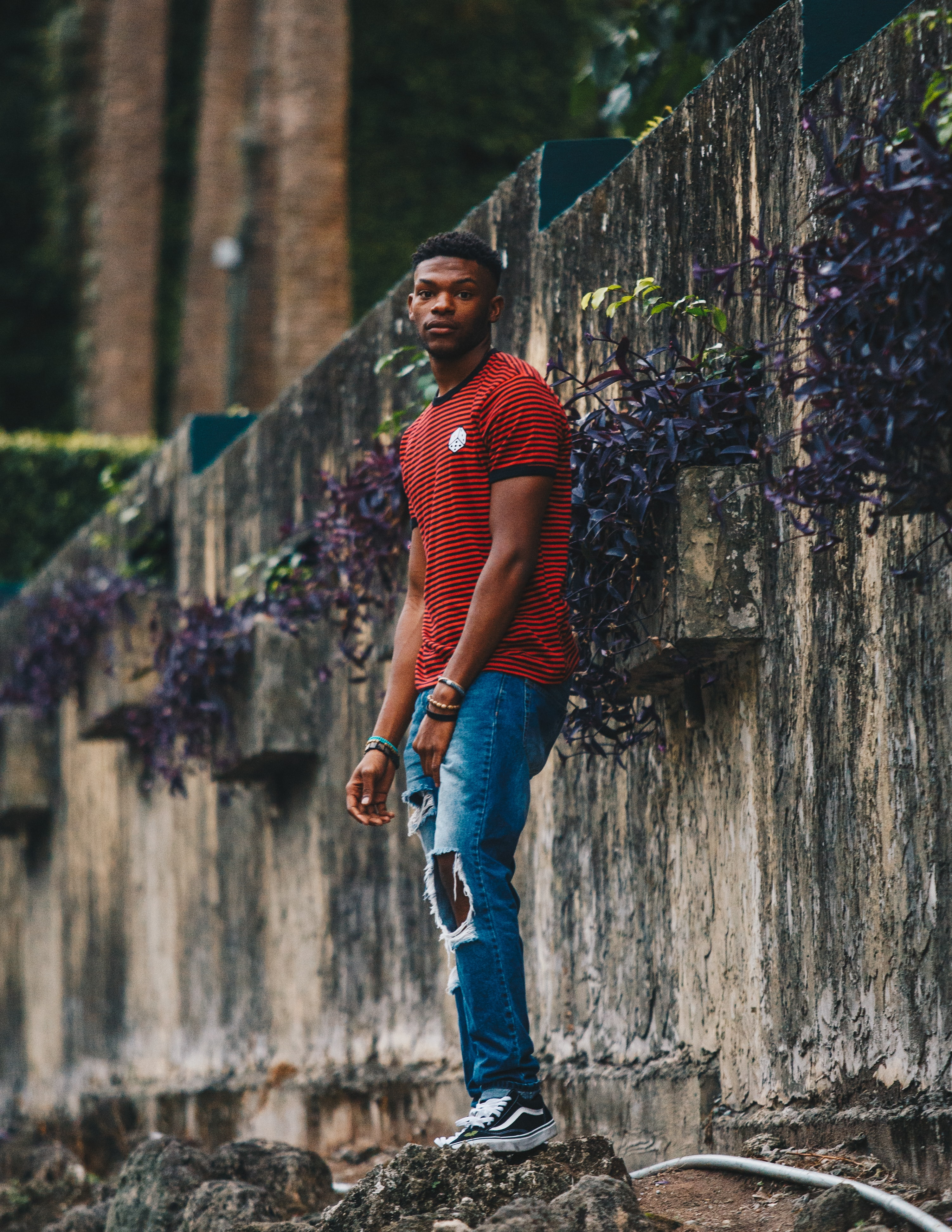 An African American man in ripped jeans and a red striped shirt.