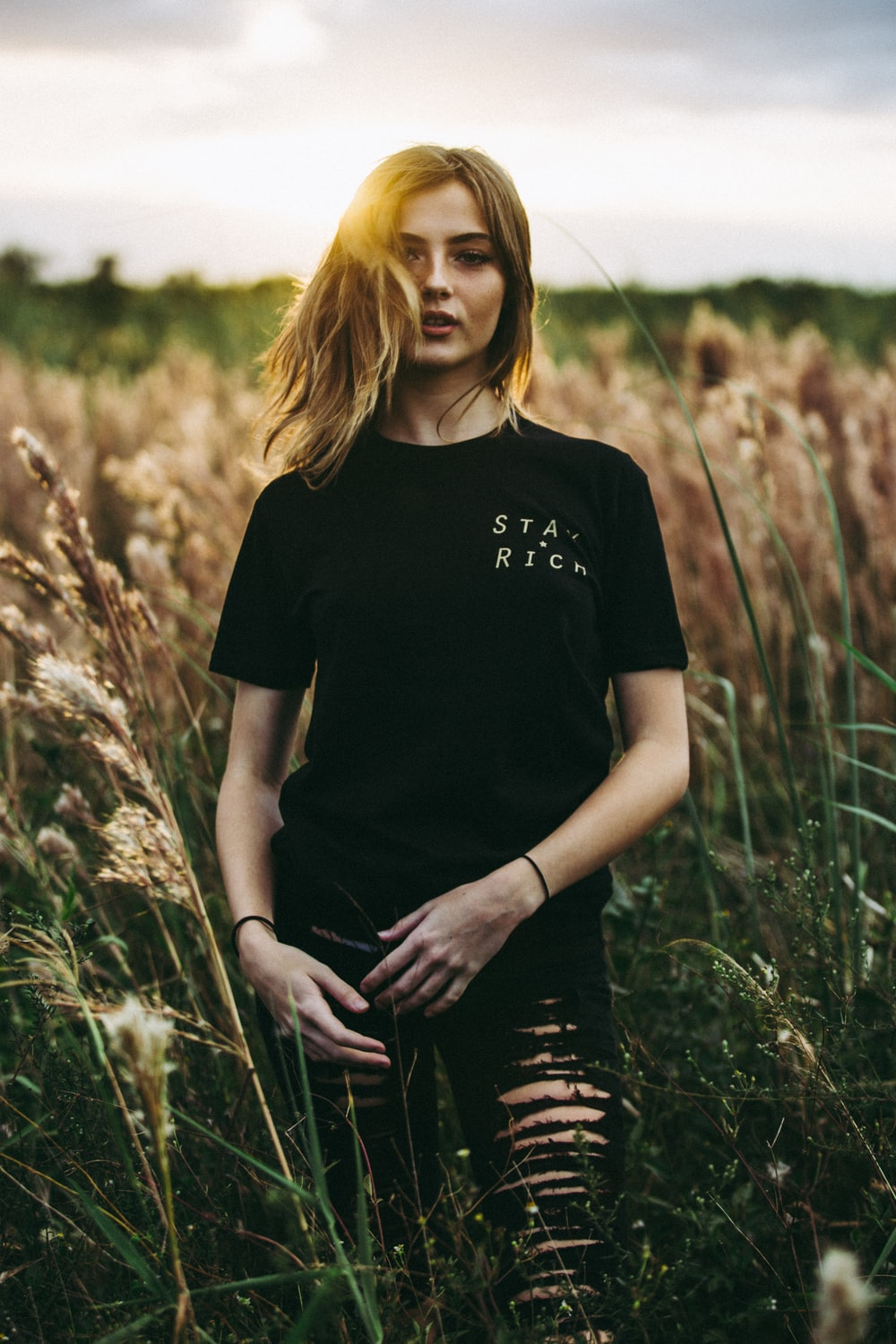 selective focus photography of black crew-neck t-shirt and distressed black bottom standing on brown wheat field during daytime