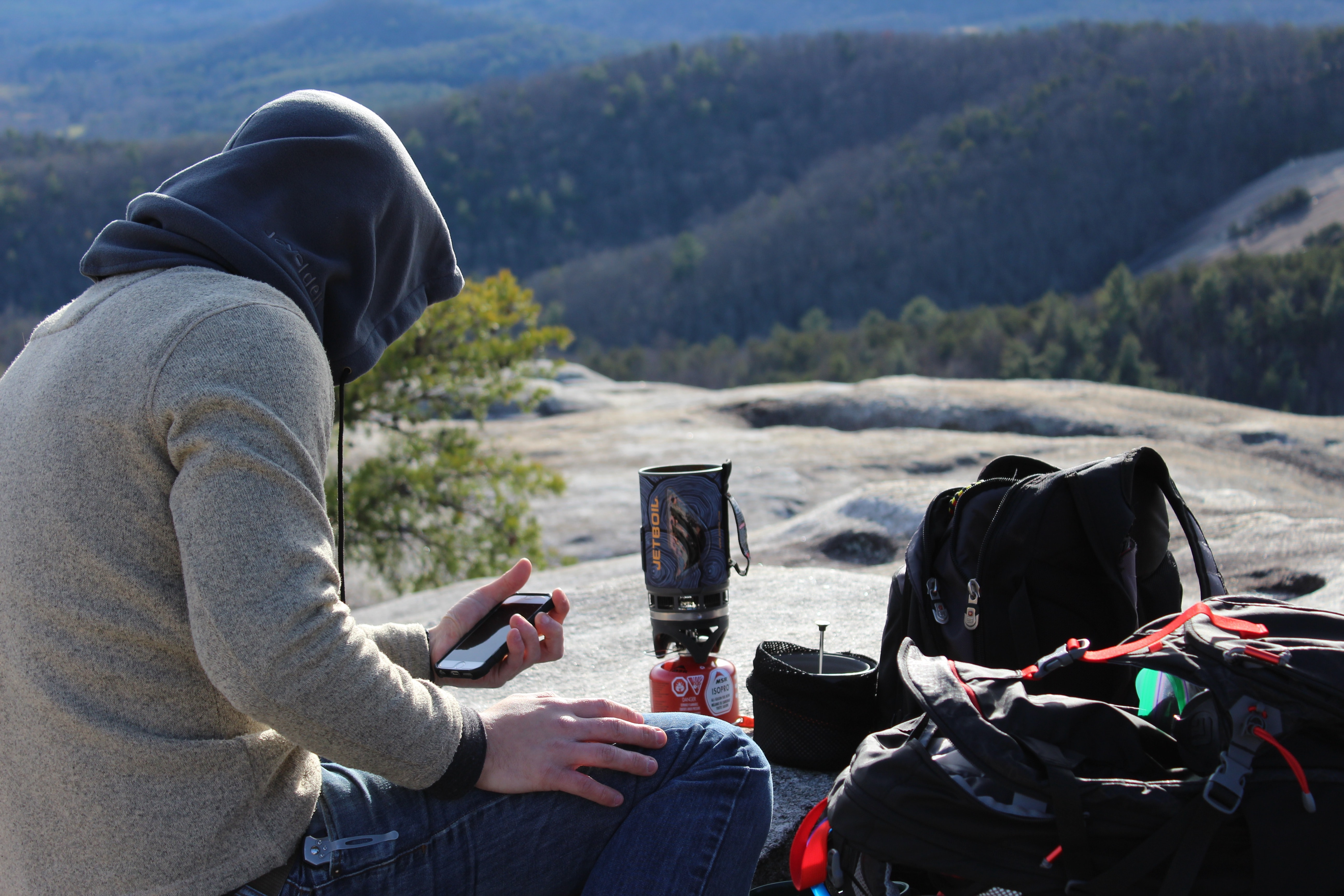 A hooded man with a phone in his hand sitting next to hiking equipment on a large rock