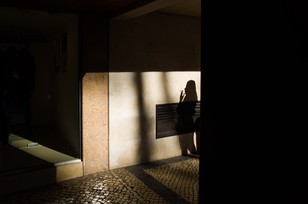 shadow of a woman smoking on brown wall