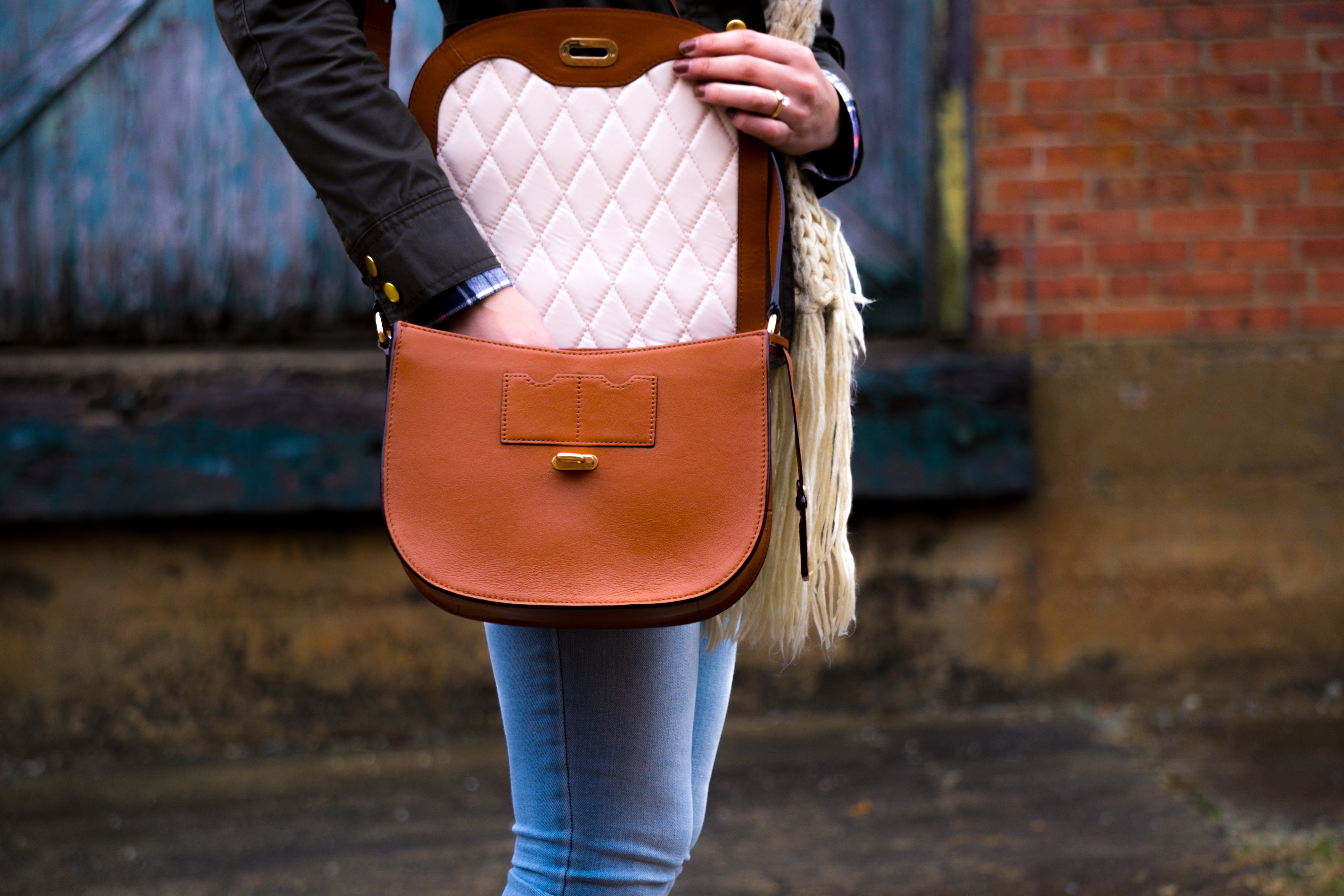 Woman reaching into her fashionable purse outside