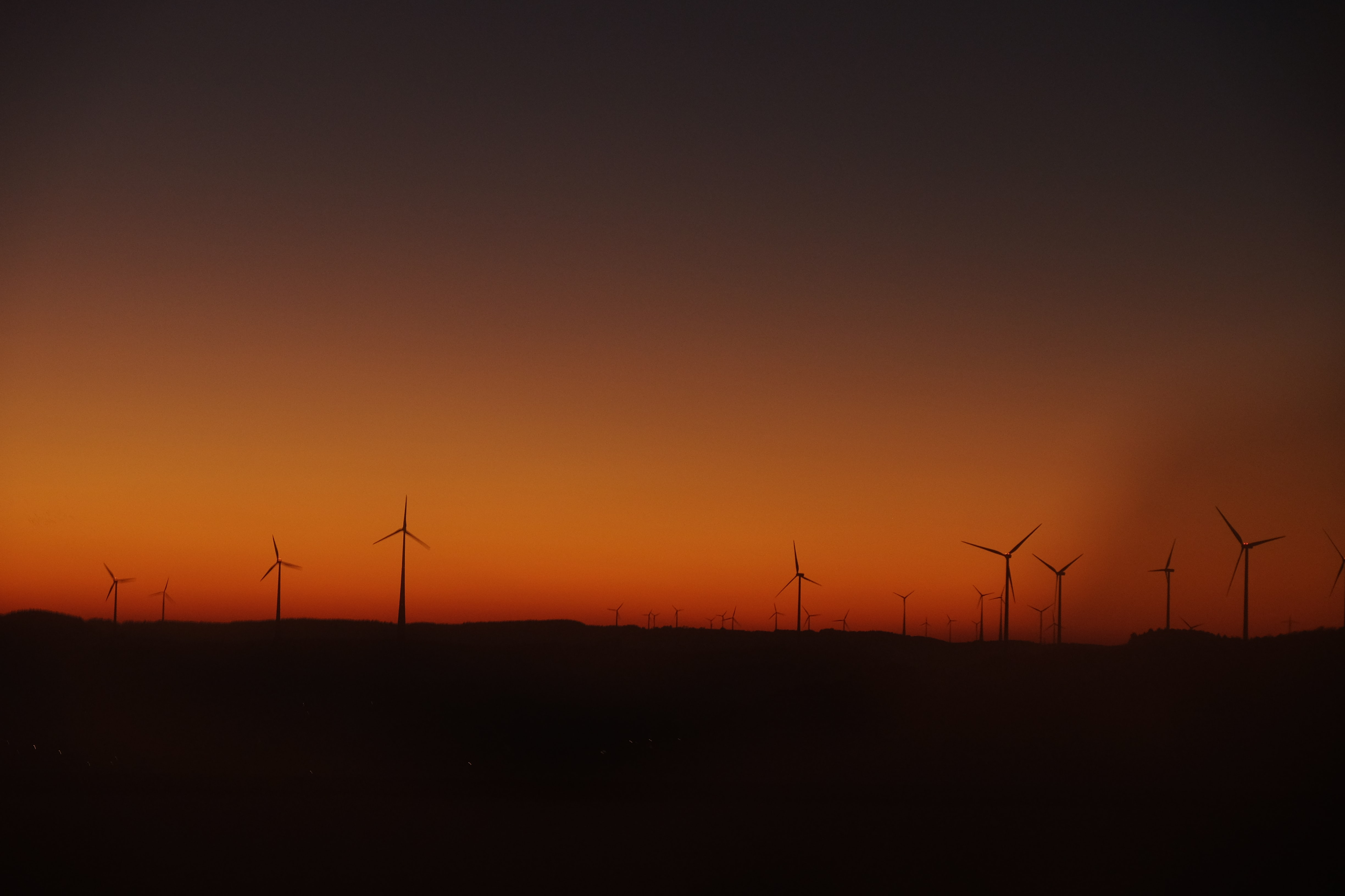 Wind turbine silhouettes at sunset against an orange and red sky in Belgium