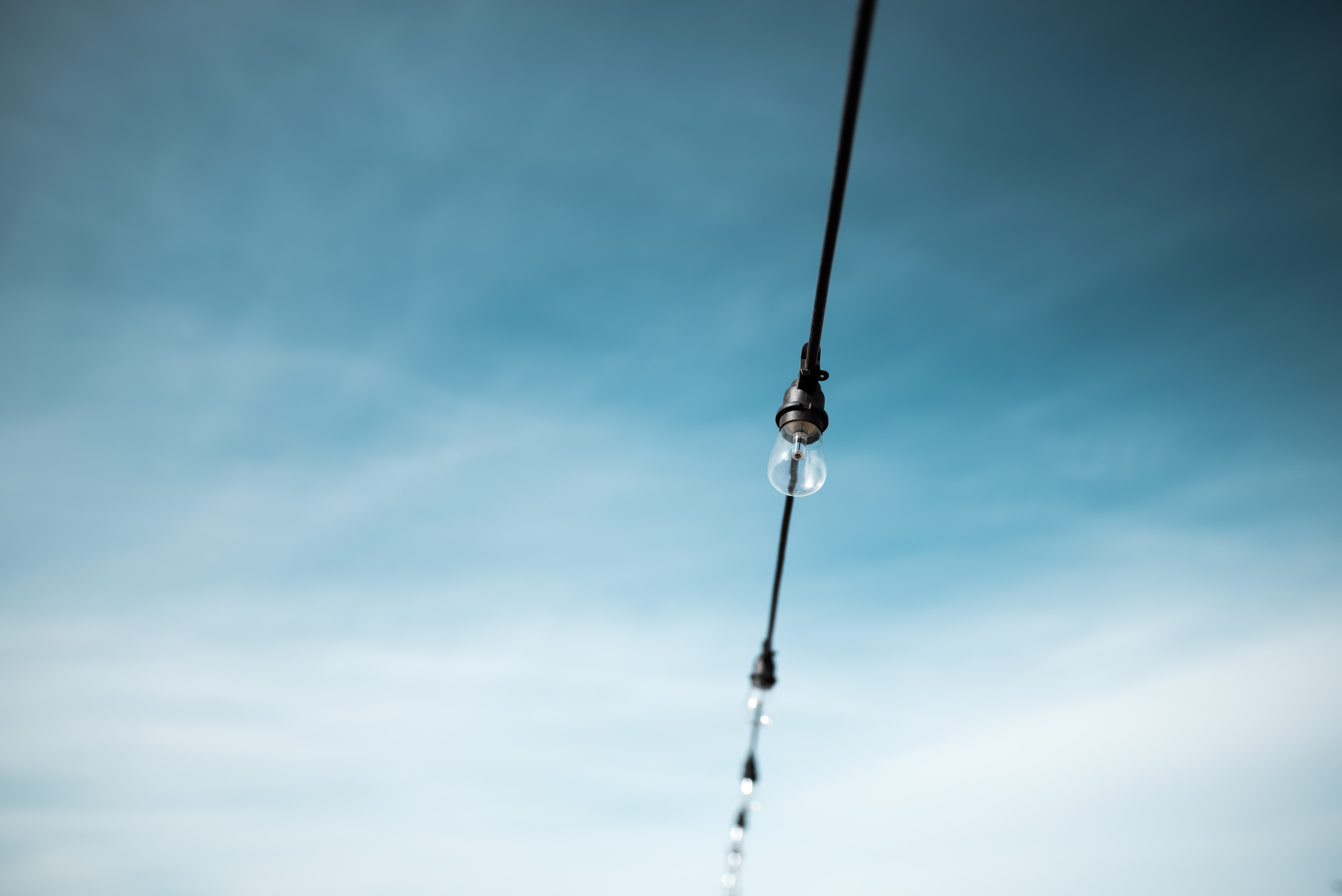 Sky lights hanging from cables underneath a blue cloudy sky