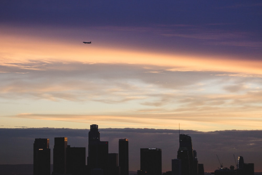 plane flying over silhouette of buildings