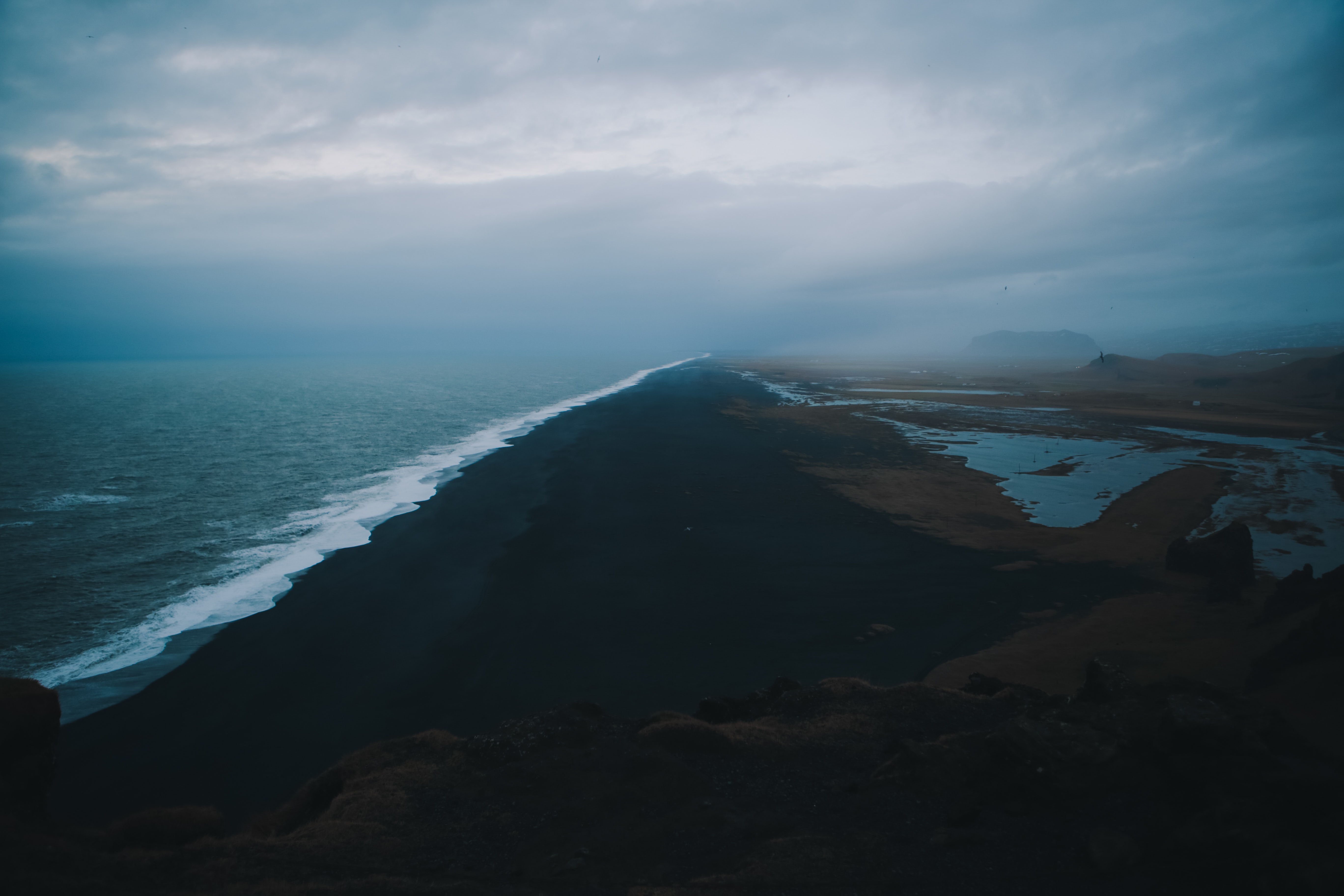 Drone view of empty Black Sand Beach shoreline on a cloudy day
