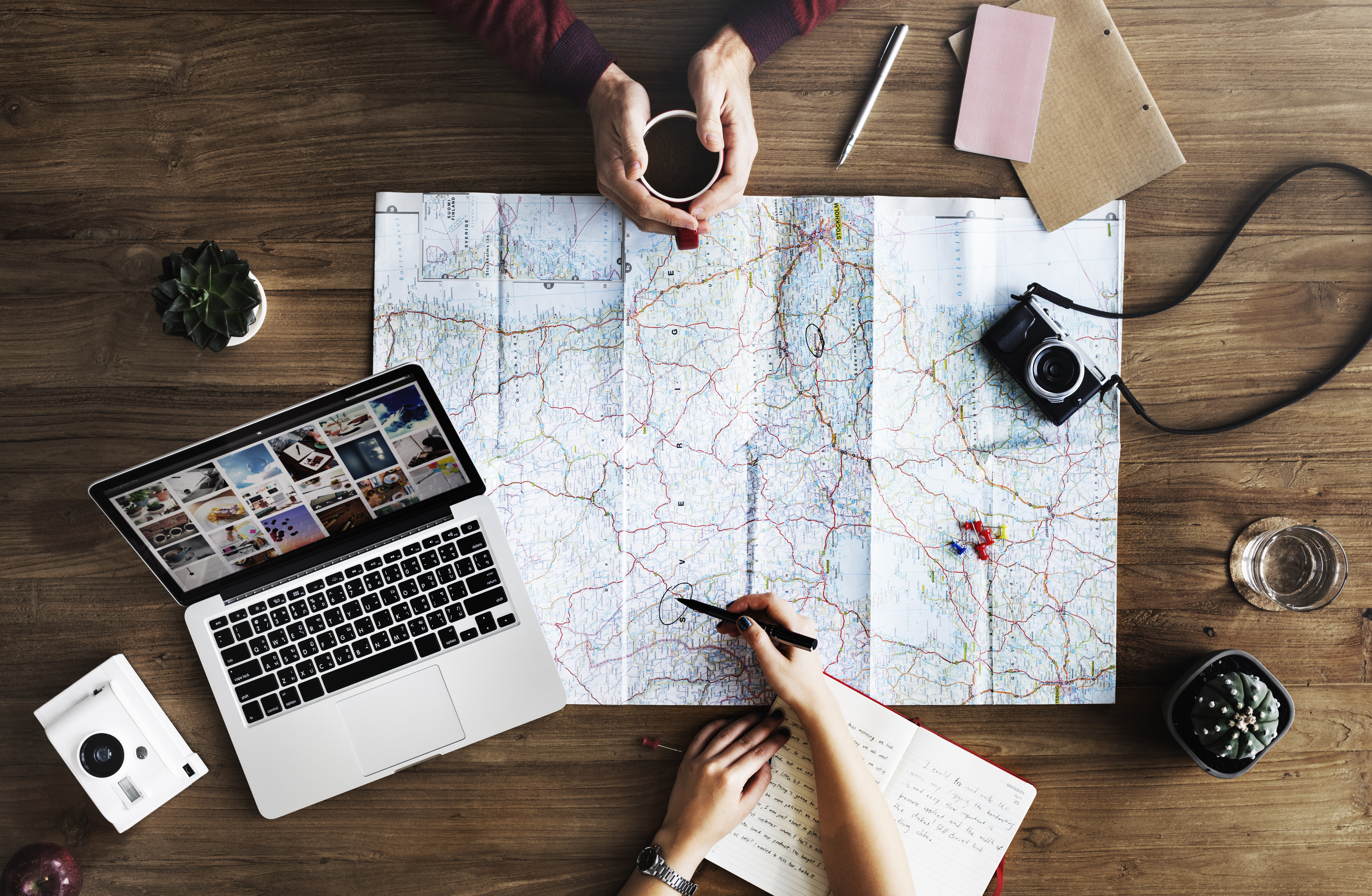 An overhead shot of two people planning a trip with a map and a laptop on a wooden surface