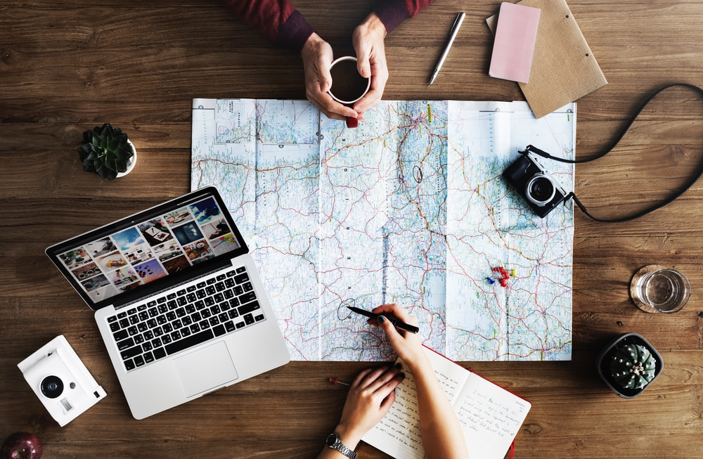 top-view photography of persons holding mug and pen using MacBook and world map planning budget travel