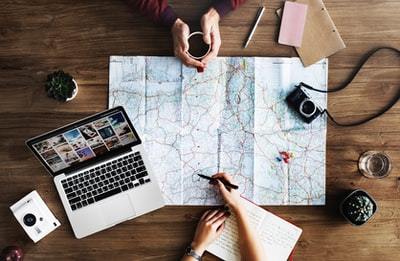 top-view photography of persons holding mug and pen using MacBook and world map