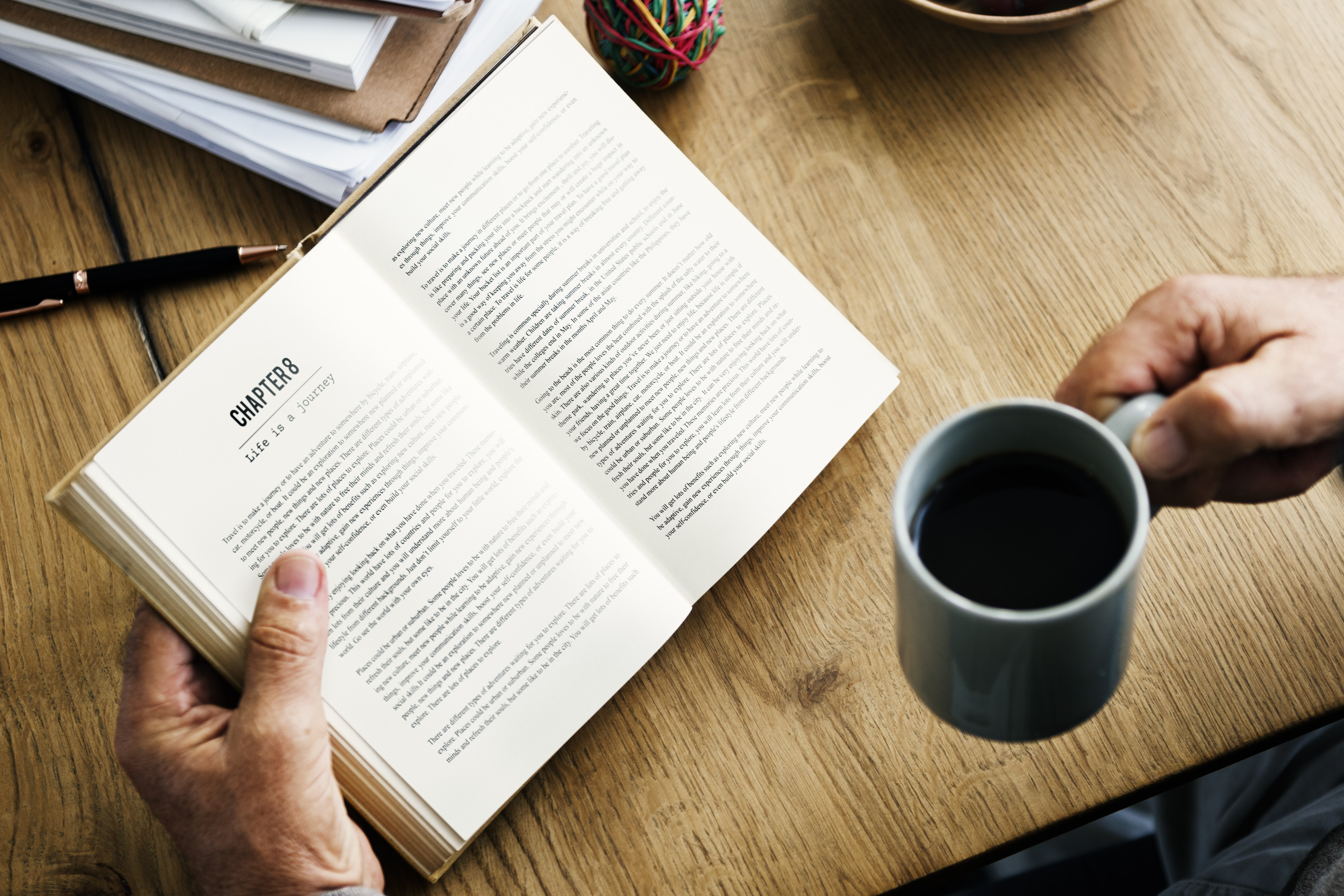 person holding blue mug and book near table